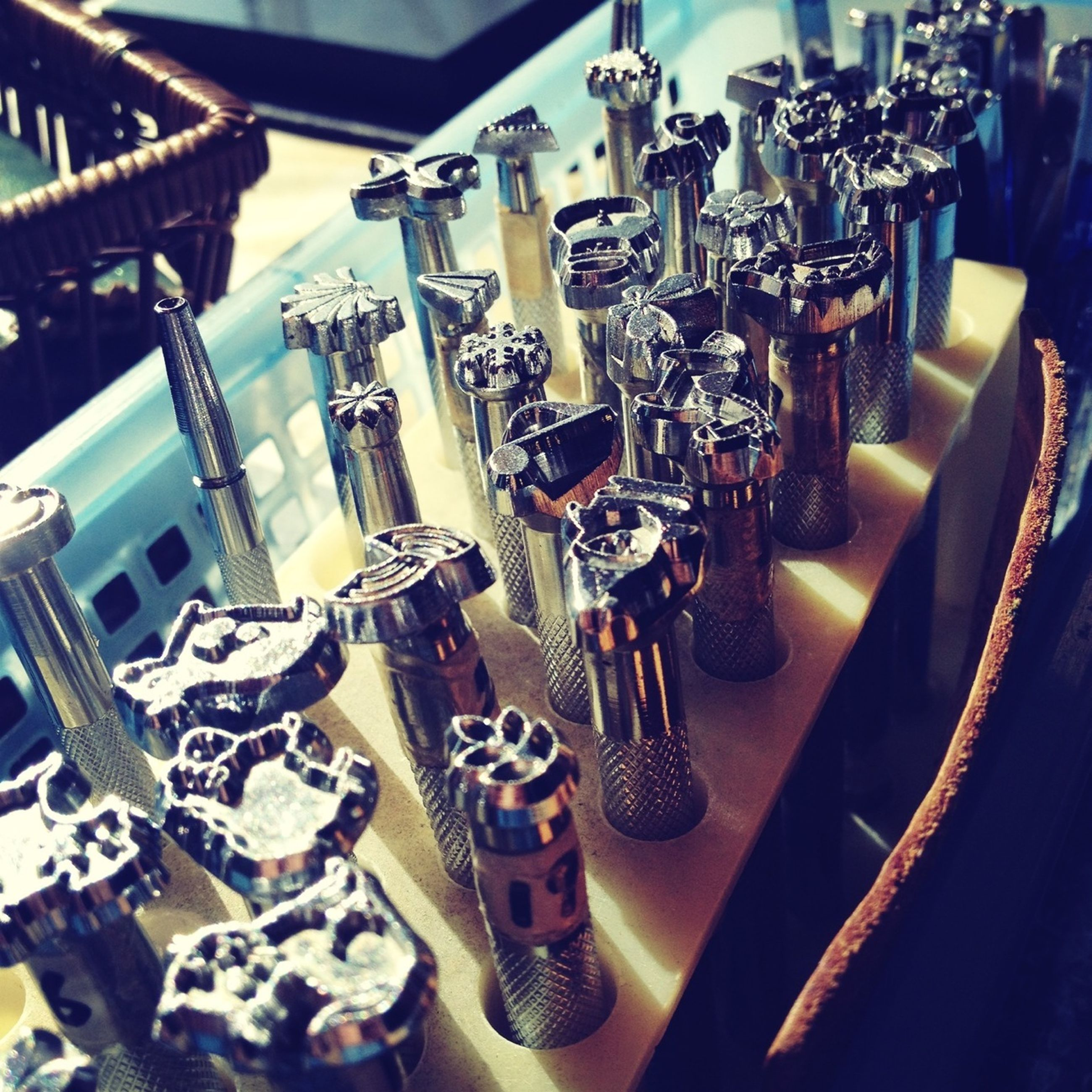 indoors, large group of objects, in a row, arrangement, abundance, still life, order, repetition, variation, close-up, hanging, choice, table, no people, metal, high angle view, arts culture and entertainment, side by side, music, luxury