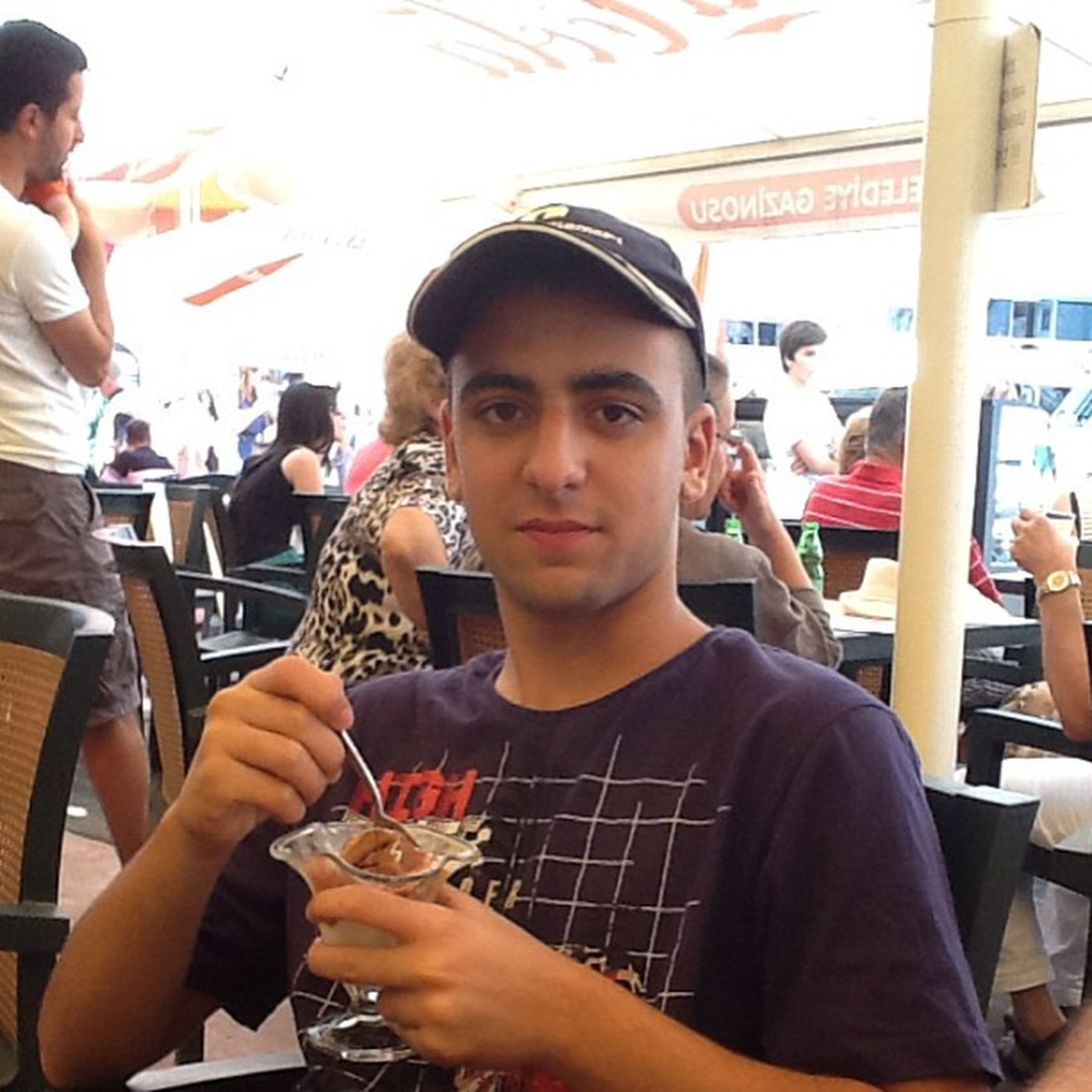 lifestyles, indoors, food and drink, leisure activity, person, holding, casual clothing, young men, communication, young adult, sitting, restaurant, portrait, front view, looking at camera, smiling, waist up, happiness