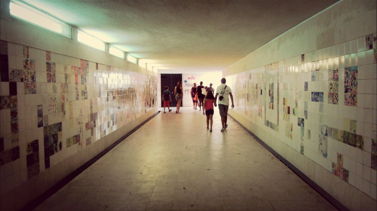 walking, real people, illuminated, indoors, men, women, the way forward, corridor, rear view, full length, leisure activity, standing, built structure, lifestyles, architecture, one person, day, adult, people