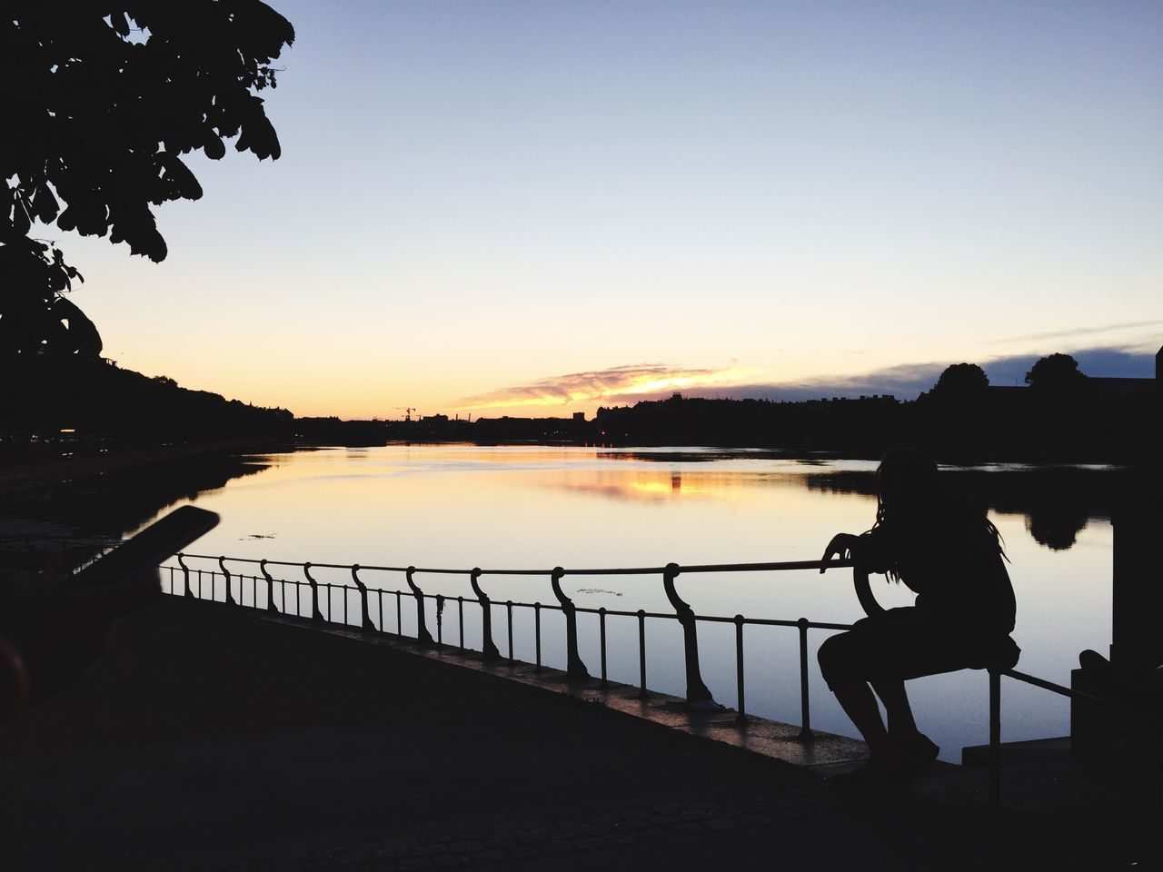 Silhouette Woman Sitting On Railing By Lake Against Sunset Sky