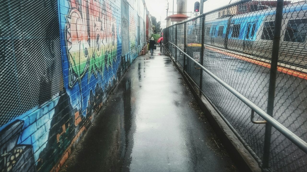 Wet Footpath Amidst Chainlink Fence And Wall