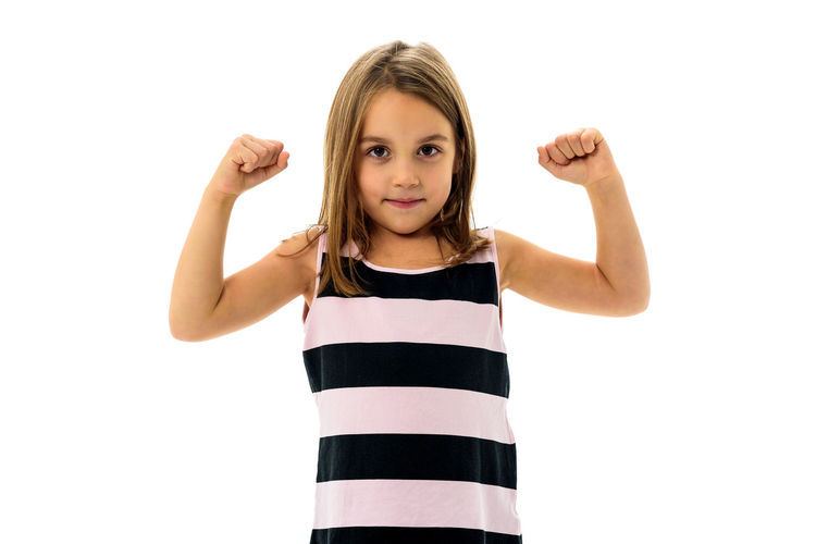 Portrait of happy young little girl showing and flexing muscles. Portrait of active little child girl flexing her arms - showing muscle. Concept of independent women and gender equality. Beautiful People Children Emotions Strong Coffee Active Arms Raised Confidence  Cute Fit Fitness Flexing Flexing Muscles Gender Equality Girl Girls Looking At Camera Muscle People Standing Strong Strong Woman Studio Shot Unbeatable White Background Young Women