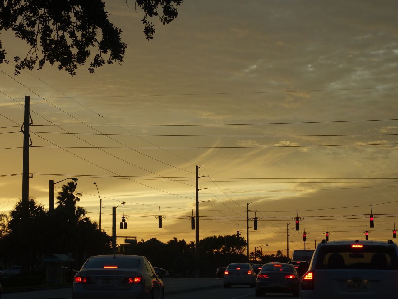 car, sunset, transportation, land vehicle, sky, road, tree, cloud - sky, mode of transport, silhouette, no people, outdoors, nature, city, electricity pylon