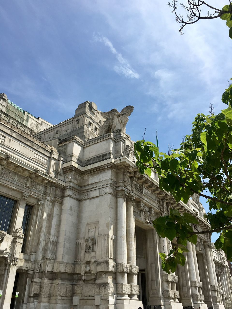 low angle view, history, architecture, built structure, statue, sky, building exterior, architectural column, ancient, sculpture, day, cloud - sky, outdoors, no people, ancient civilization, tree
