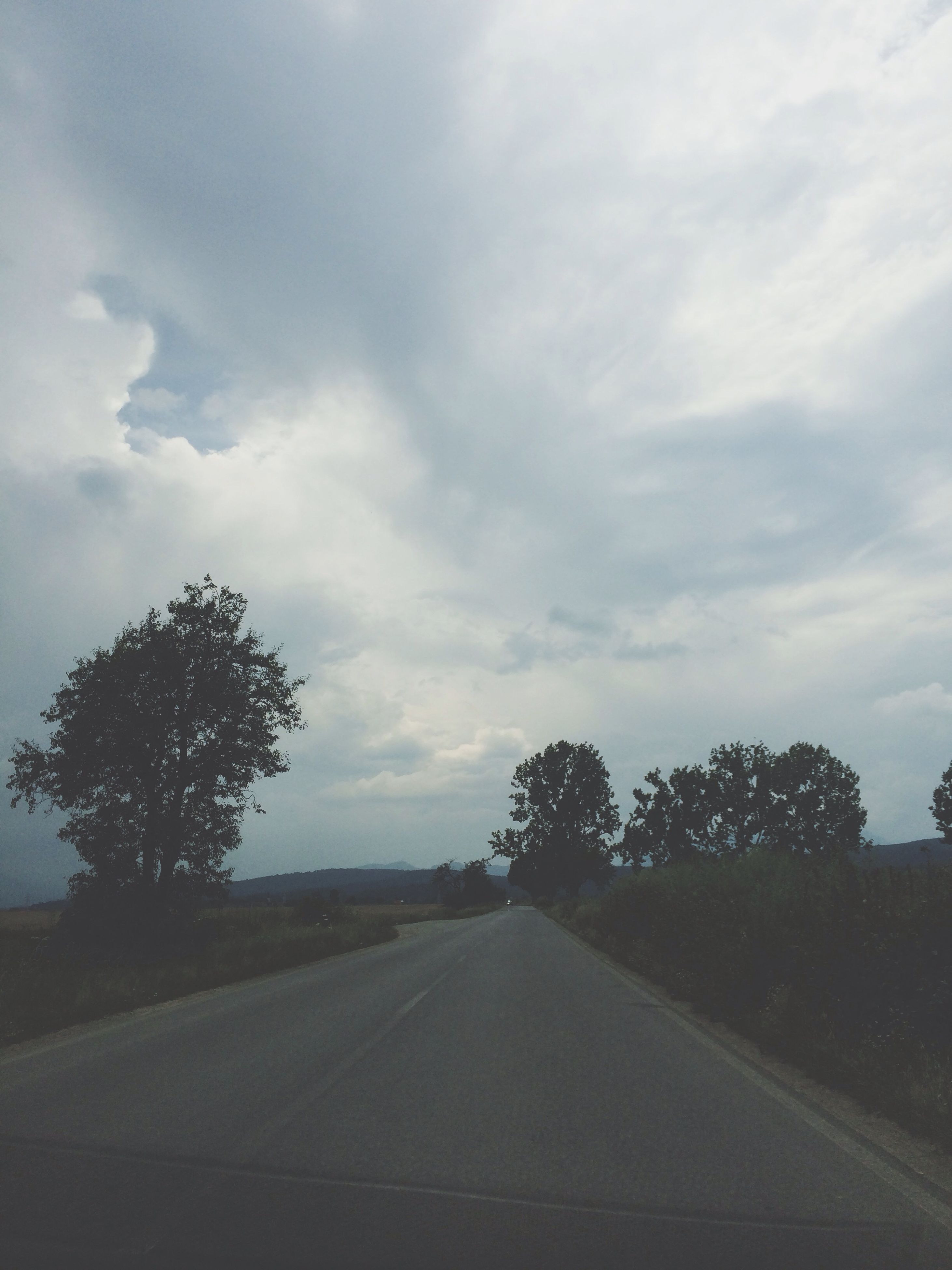 sky, the way forward, road, transportation, tree, cloud - sky, diminishing perspective, tranquility, cloudy, vanishing point, tranquil scene, road marking, cloud, landscape, country road, nature, empty road, empty, scenics, beauty in nature