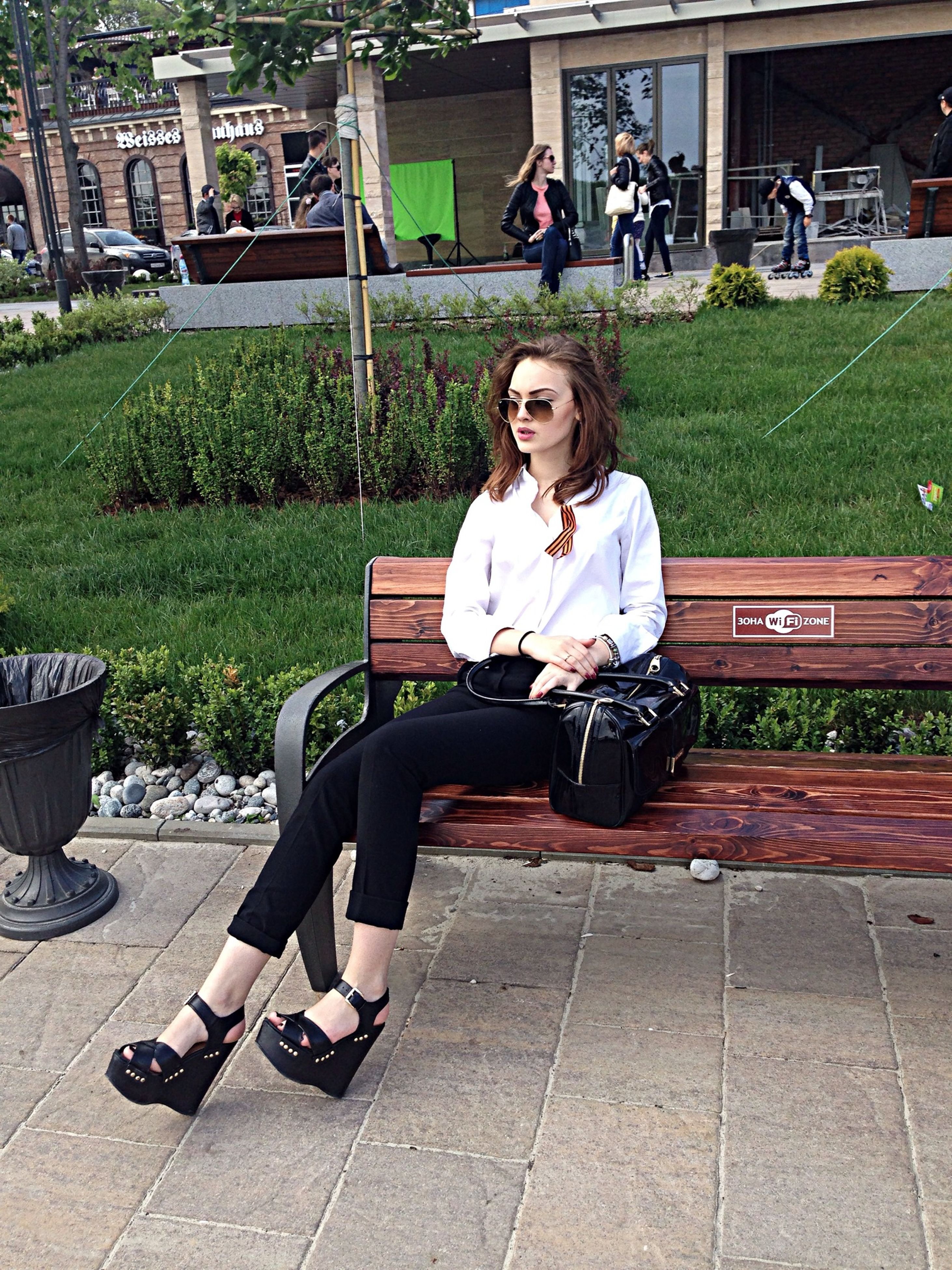 sitting, lifestyles, full length, casual clothing, leisure activity, relaxation, person, young adult, park - man made space, bench, young women, chair, grass, outdoors, day, park, childhood, building exterior