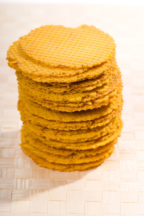 Cheesy taste wafers stack lying on beige mat on table. Food snack prepared and ready to eat, standing on mat, vertical orientation, objects in studio shot. Biscuit Cheese Cheesey Cheesy Cookie Crisp Crispy Crunch Crunch Time Crunchy Dessert Flat Food No People Pile Products Roasted Snack Snacks Stack Tidbits Wafer Wafer Rolls Waffers Yellow