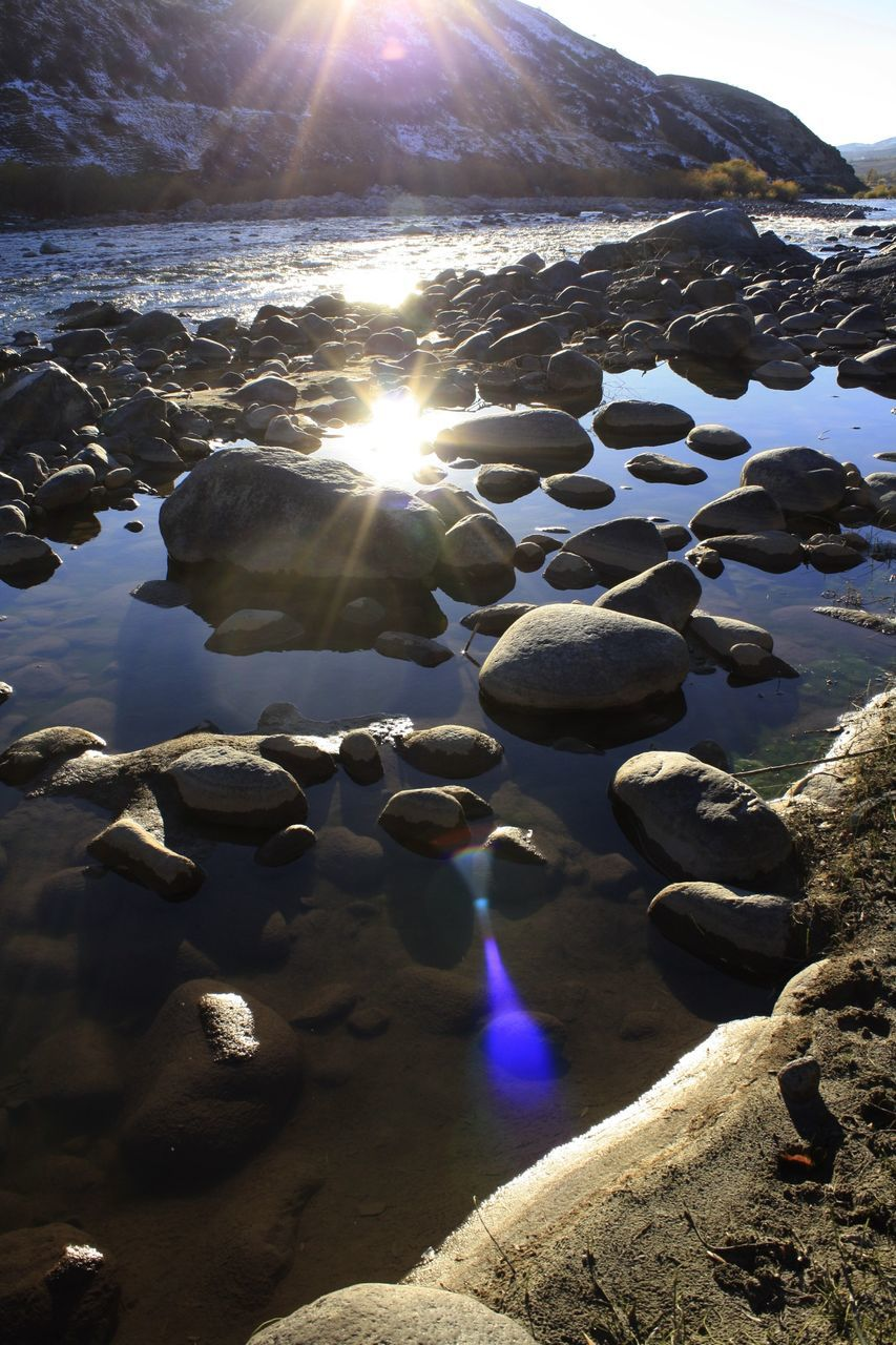 sunlight, sunbeam, lens flare, sun, outdoors, beach, no people, nature, day, sand, tranquility, beauty in nature, water, pebble, close-up, pebble beach