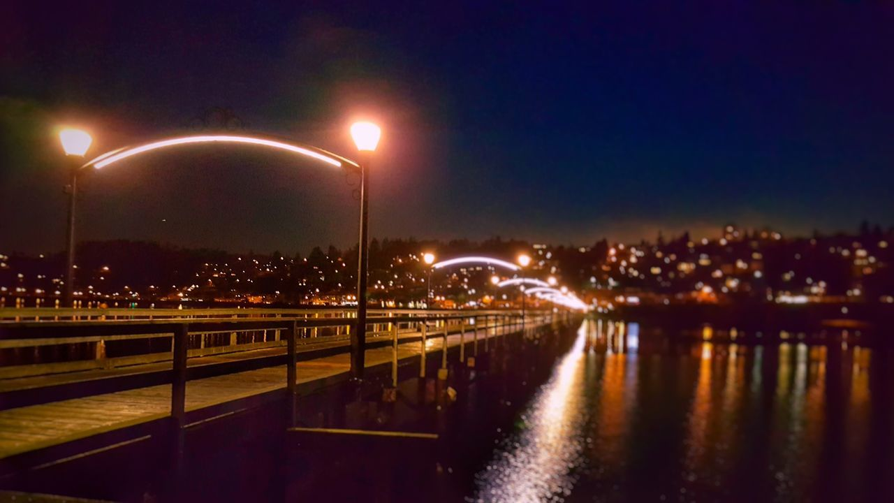 Street Light Illuminated Night Water Road Bridge Railing Reflection Canal Dark Long Sky City Life Lit Promenade Waterfront Solitude Orange Color Outdoors Multi Colored Beauty In Nature Calm Cloud Tranquility Harbor