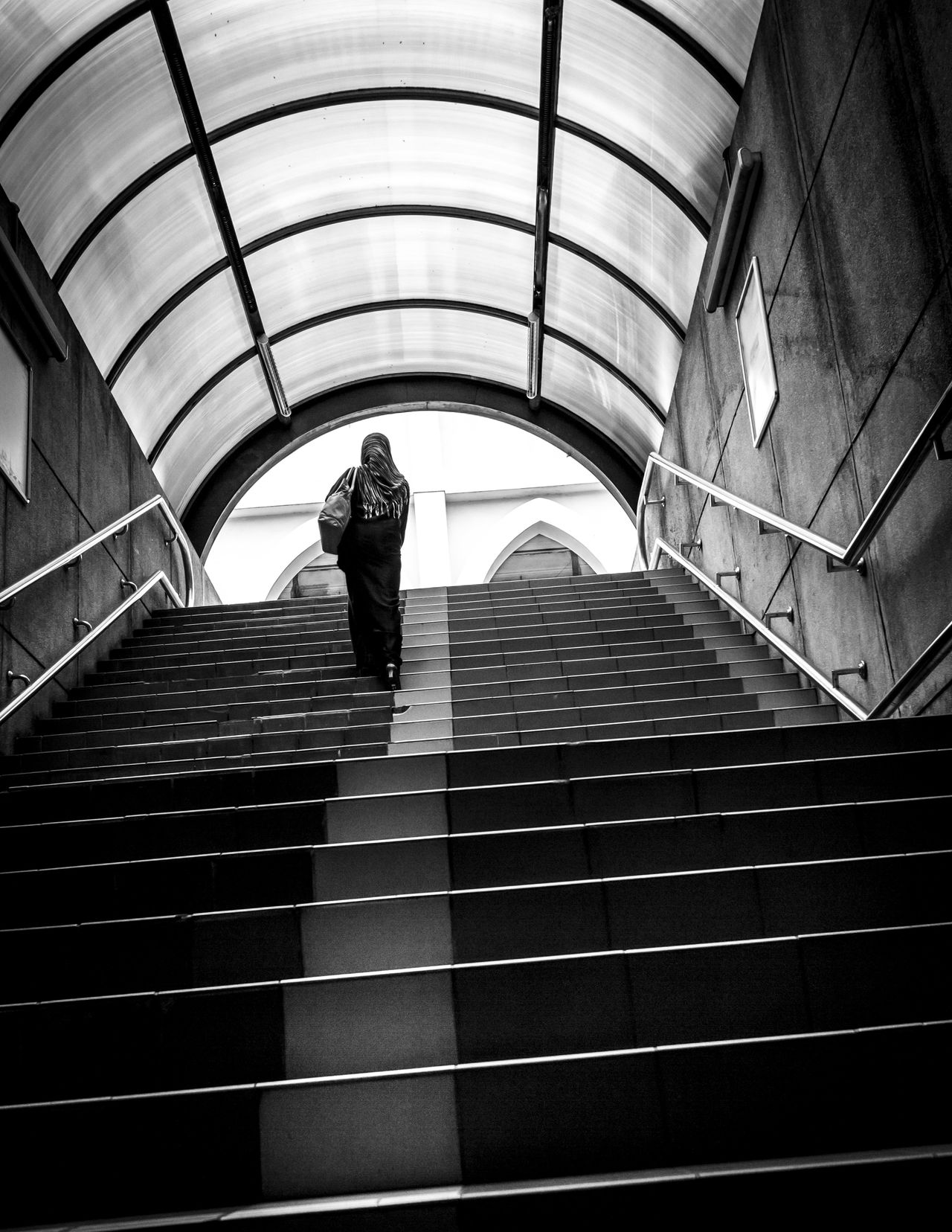 Woman walking up steps from underground tunnel Alone Arch Architecture Ascending B&w Photography Blackandwhite Built Structure City Exit Going Up Low Angle View Muslim Perspective Rear View Staircase Stairs Steps Steps And Staircases Streetphotography The Way Forward Tunnel Up Urban Walking Woman