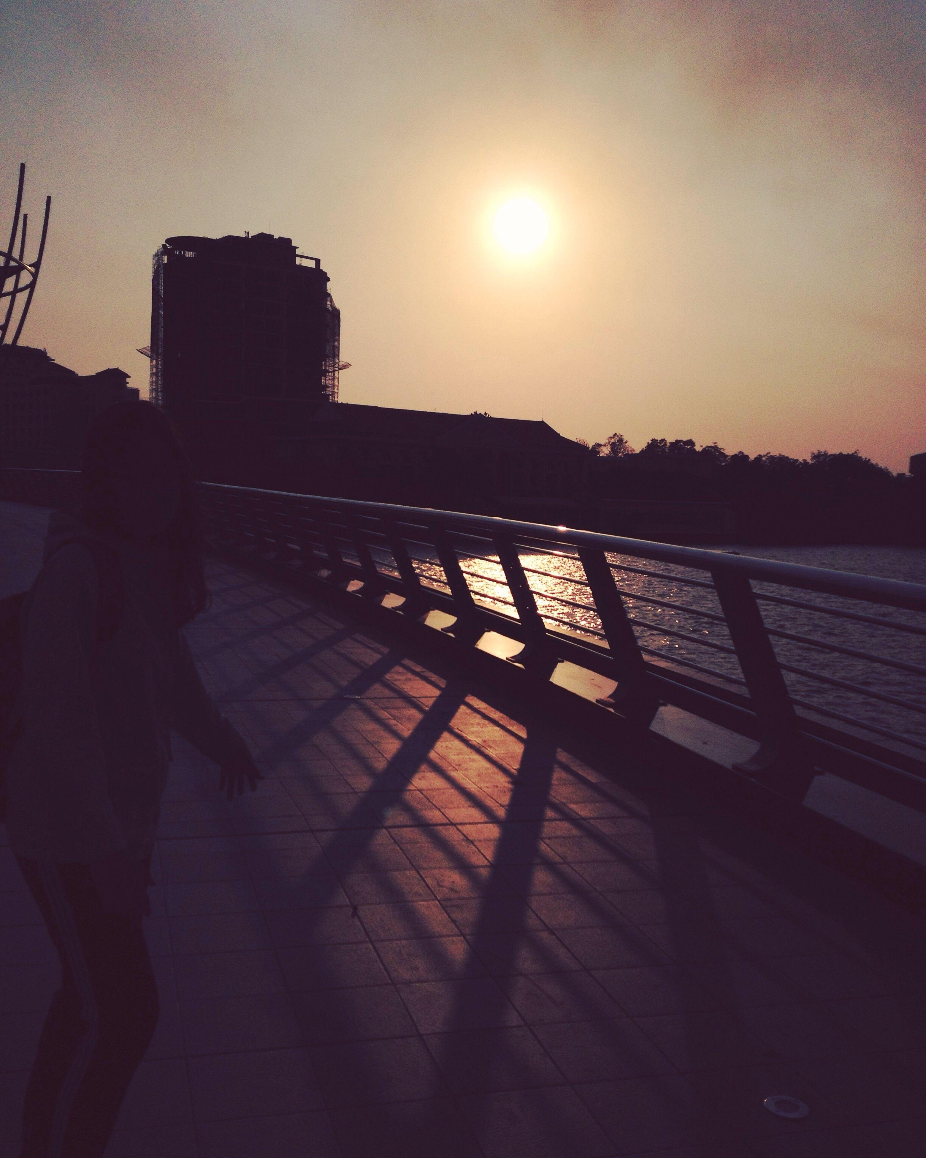 sunset, sun, silhouette, built structure, building exterior, architecture, sunlight, sky, sunbeam, lens flare, railing, clear sky, city, outdoors, orange color, shadow, reflection, building