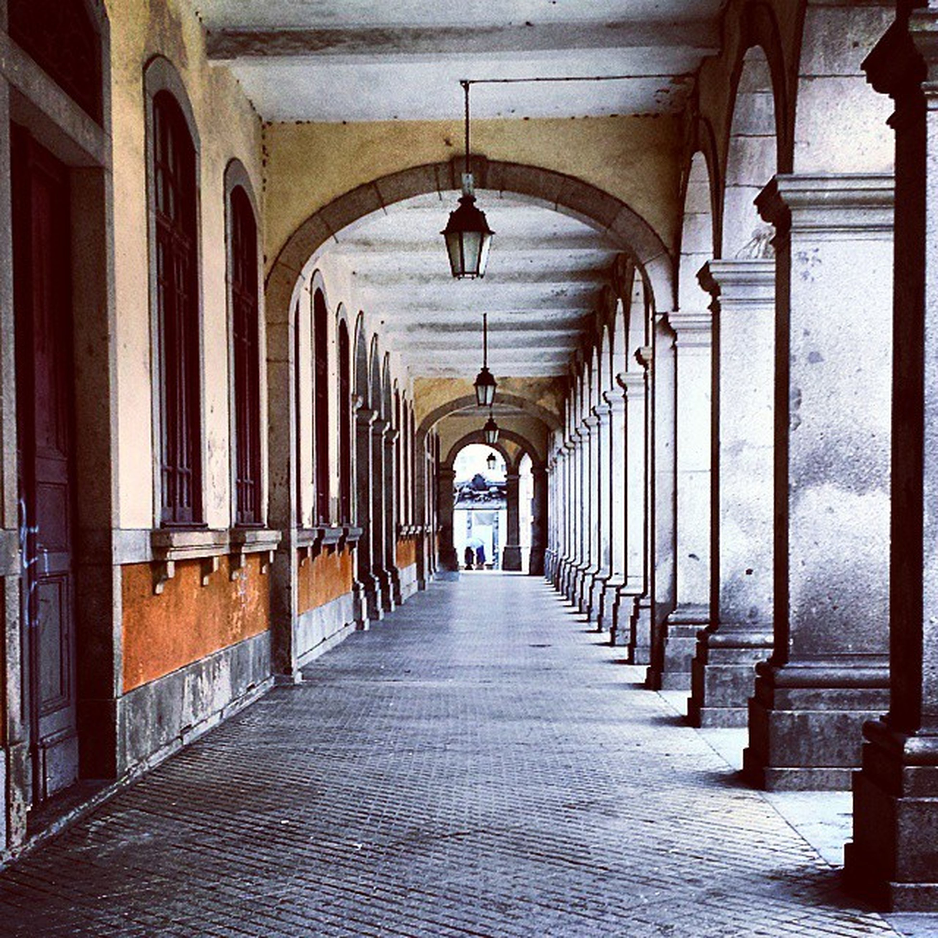 indoors, architecture, the way forward, corridor, built structure, diminishing perspective, ceiling, arch, architectural column, in a row, colonnade, empty, vanishing point, column, interior, flooring, history, building, long, narrow