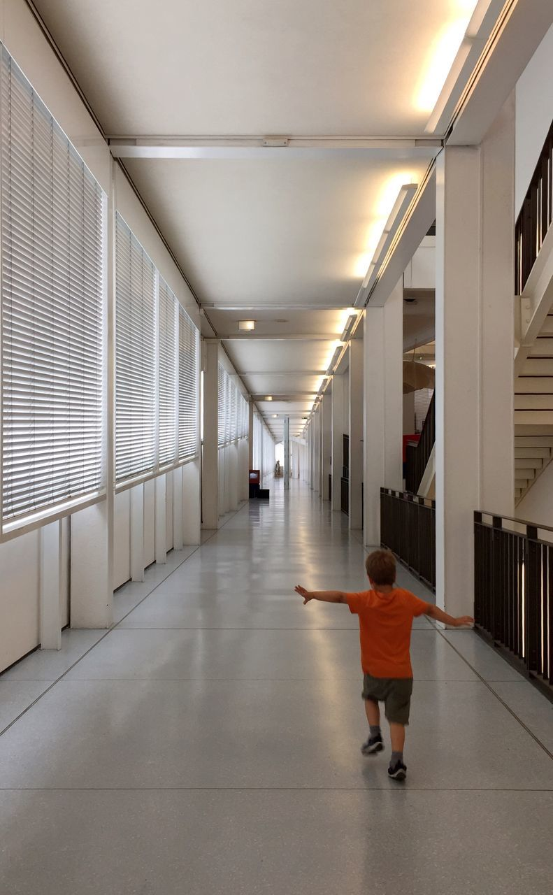 Full Length Rear View Of Boy With Arms Outstretched Running In Corridor
