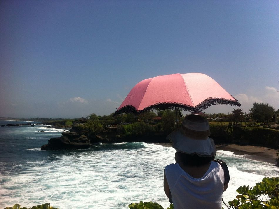 Pura Tanah Lot, Bali Bali Beach Beauty In Nature Clear Sky Day Horizon Over Water INDONESIA Island Landscape Leisure Activity Nature One Person Outdoors People Pink Plant Real People Scenics Sea Sightseeing Sky Standing Tanah Lot Temple Water