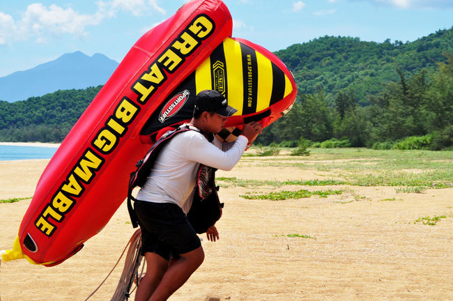 Resort workers carrying inflatable ride on beach at Lang Co, Vietnam. Action Beaches Carrying Casual Clothing Color Of Sport Editorial  Inflatables Lang Co Beach Leisure Lifestyle Mountains Outdoors Resorts Sand Service Sunlight Text Tourism Travel Vietnam Watercraft Workers