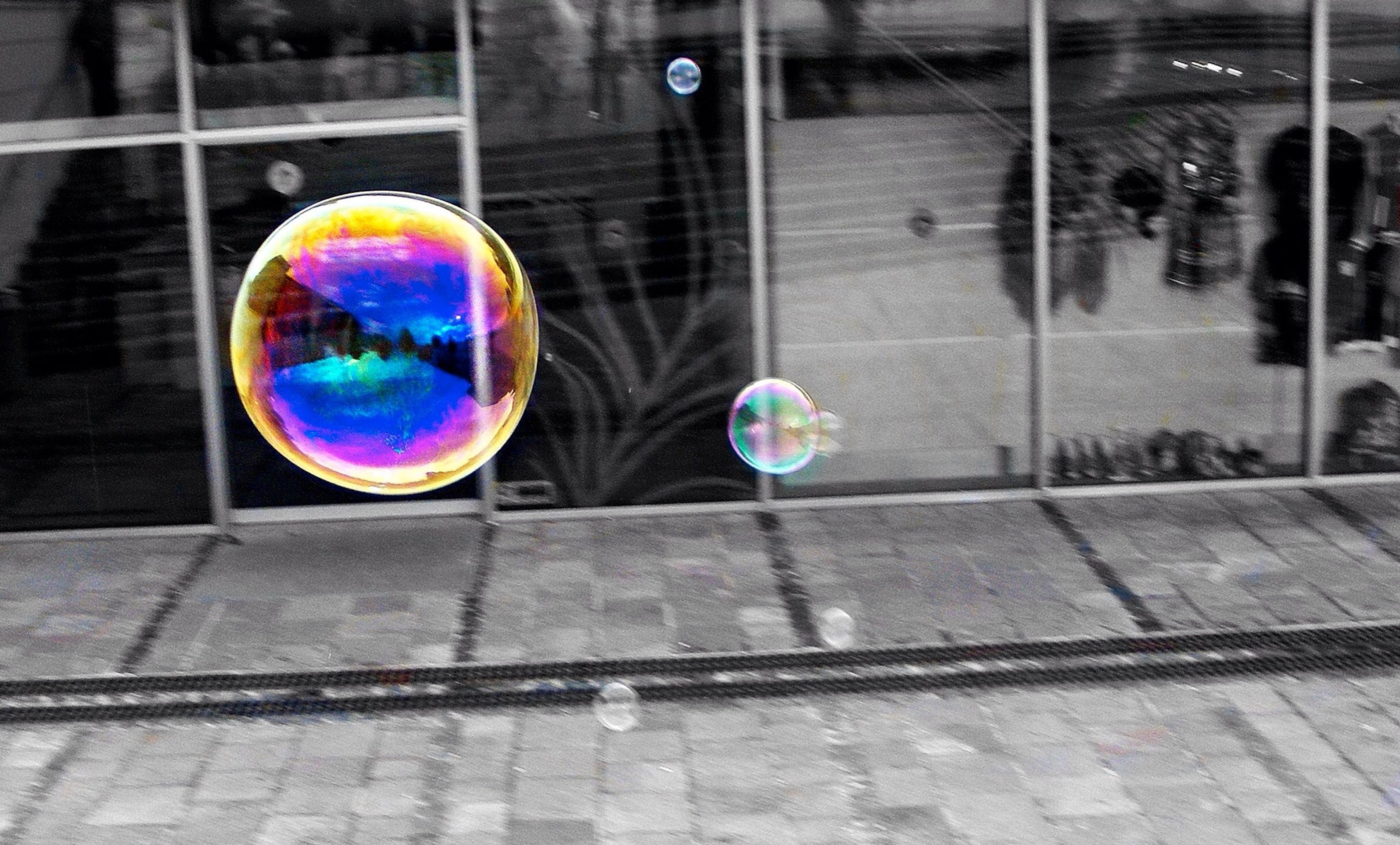 sphere, multi colored, street, mid-air, focus on foreground, transportation, ball, reflection, balloon, close-up, outdoors, road, incidental people, fragility, glass - material, circle, day, no people, motion, colorful