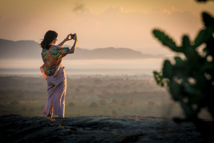 Adult Adults Only Adventure Beach Beauty In Nature Camera - Photographic Equipment Dambulla Day Full Length Lion Mountain Multi Colored One Person One Woman Only Outdoors People Photographer Photography Themes Pidurangala Rock Romantic Sky SriLanka Sunrise Sunset Travel Destinations
