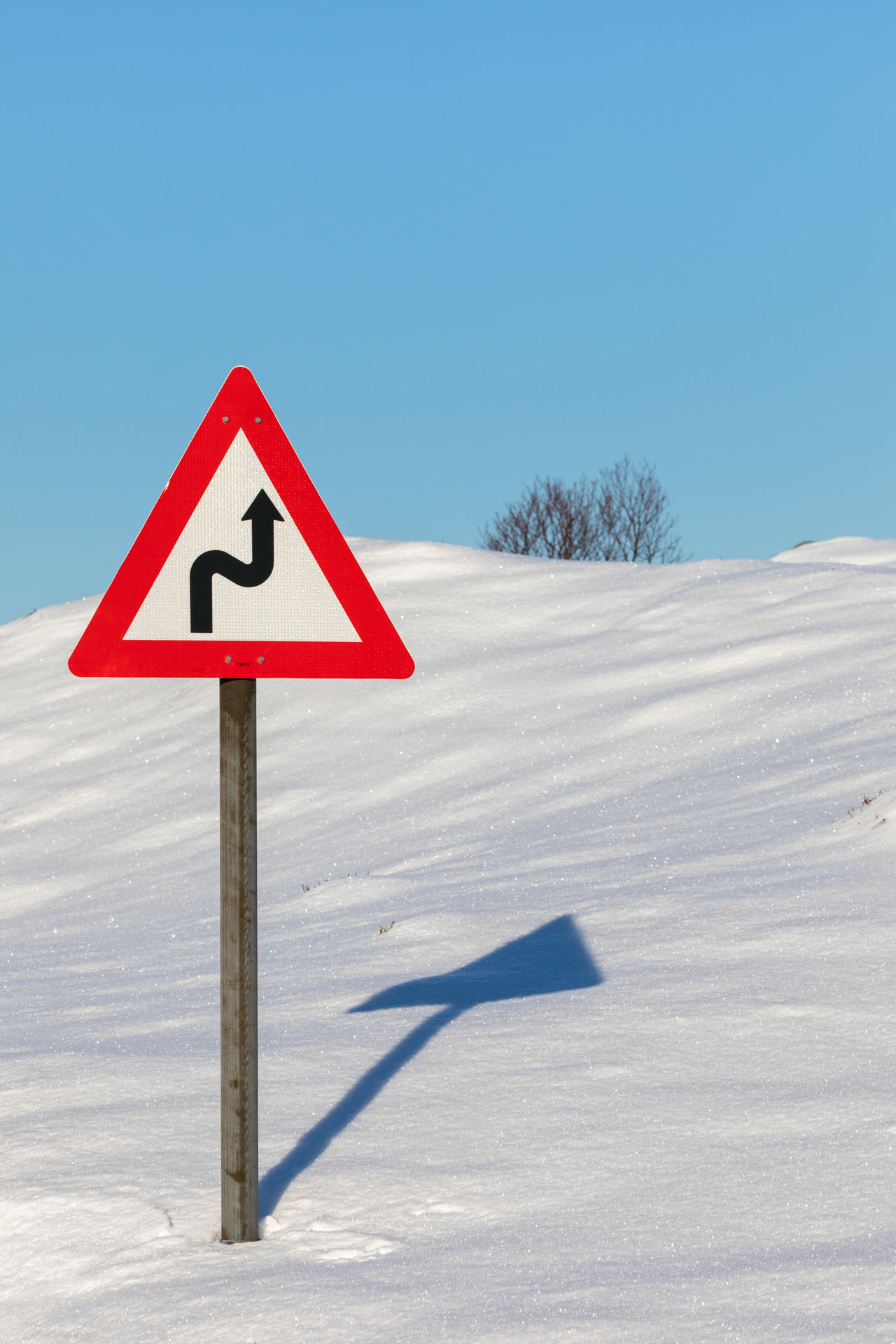 Road warning sign for winding road in deep snow Arrow Symbol Blue Clear Sky Danger Deep Snow Direction Double Bend Sign Guidance Lofoten And Vesteral Islands Red Road Sign S-shape Safety Shadow Sky Snow Sunny Symbol Traffic Arrow Sign Tree Triangle Shape Turning Warning Sign Winding Road Winter