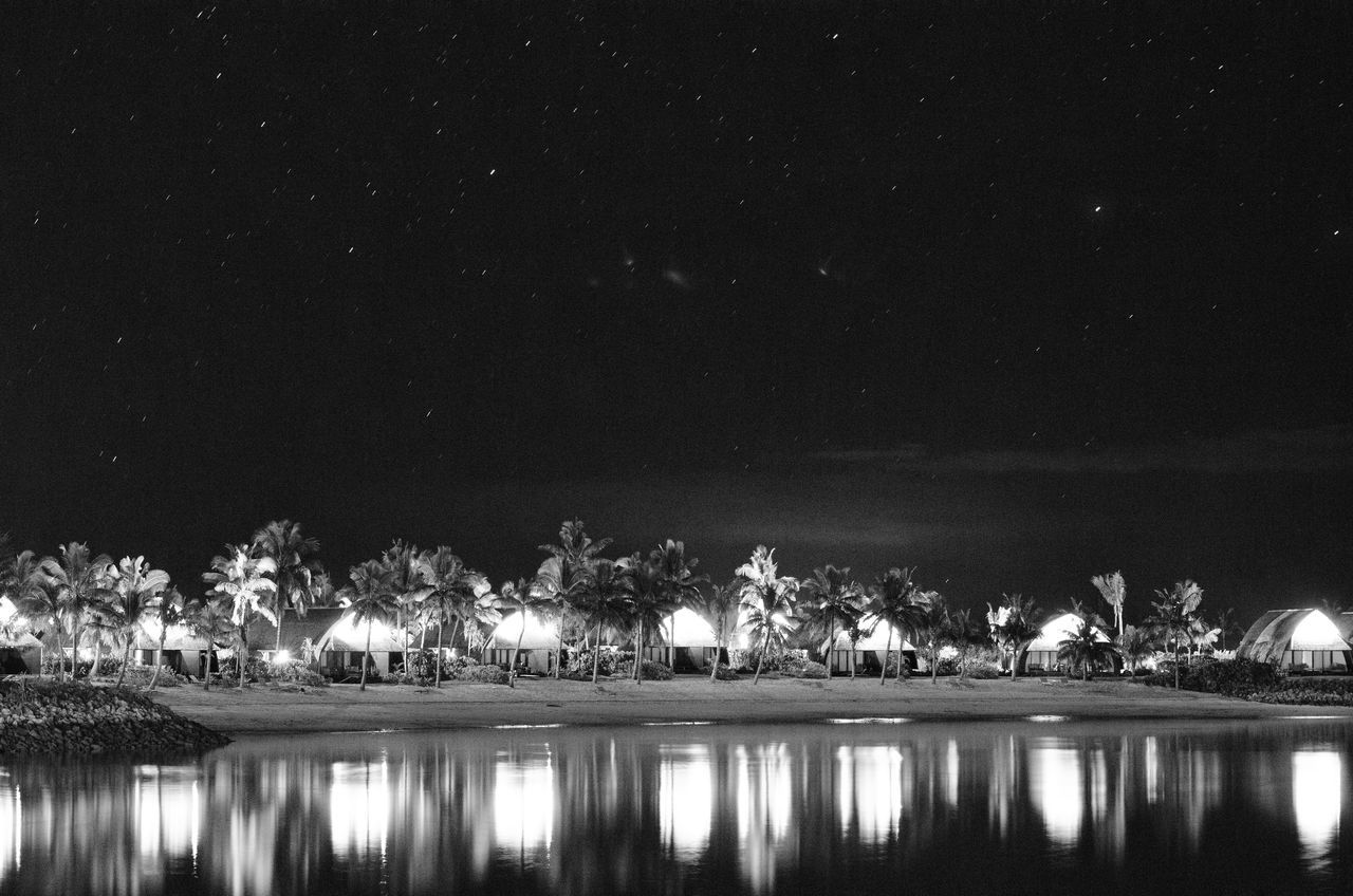 Bures under the stars in B&W Beauty In Nature Black And White Bure Fiji Illuminated Lagoon Nature Night Night Photography No People Outdoors Palm Trees Reflection Scenics Sky Tree Water Waterfront