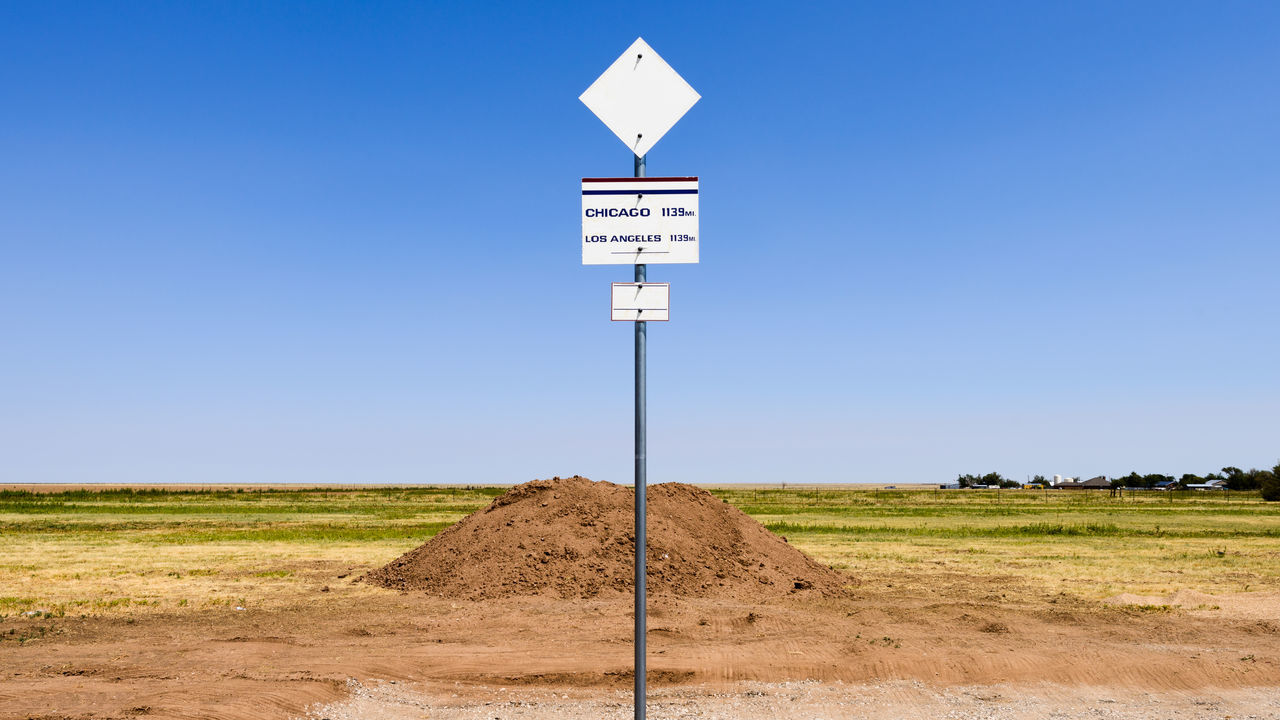 Road Sign On Field Against Clear Sky