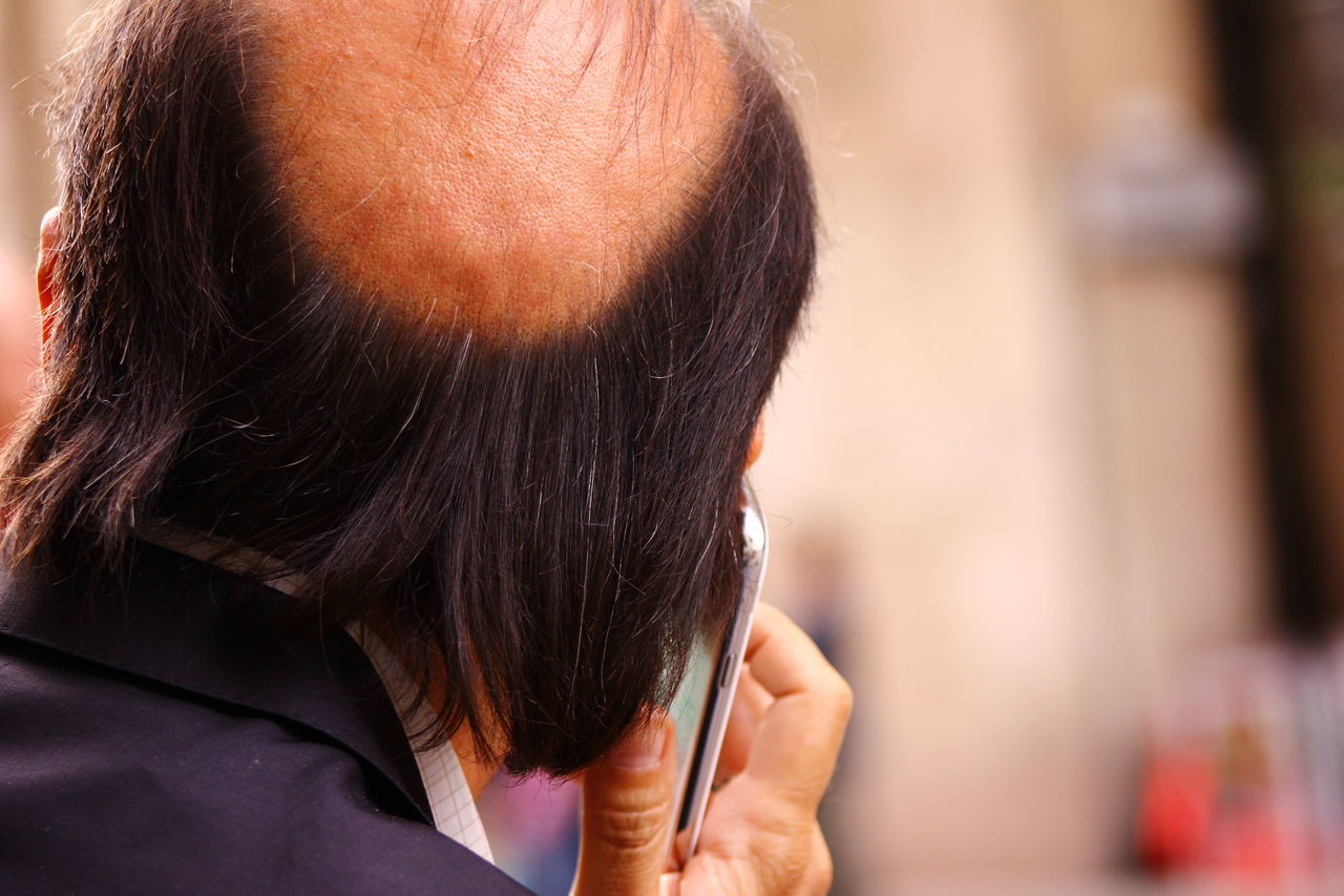 Rear View Of Man Using Smart Phone