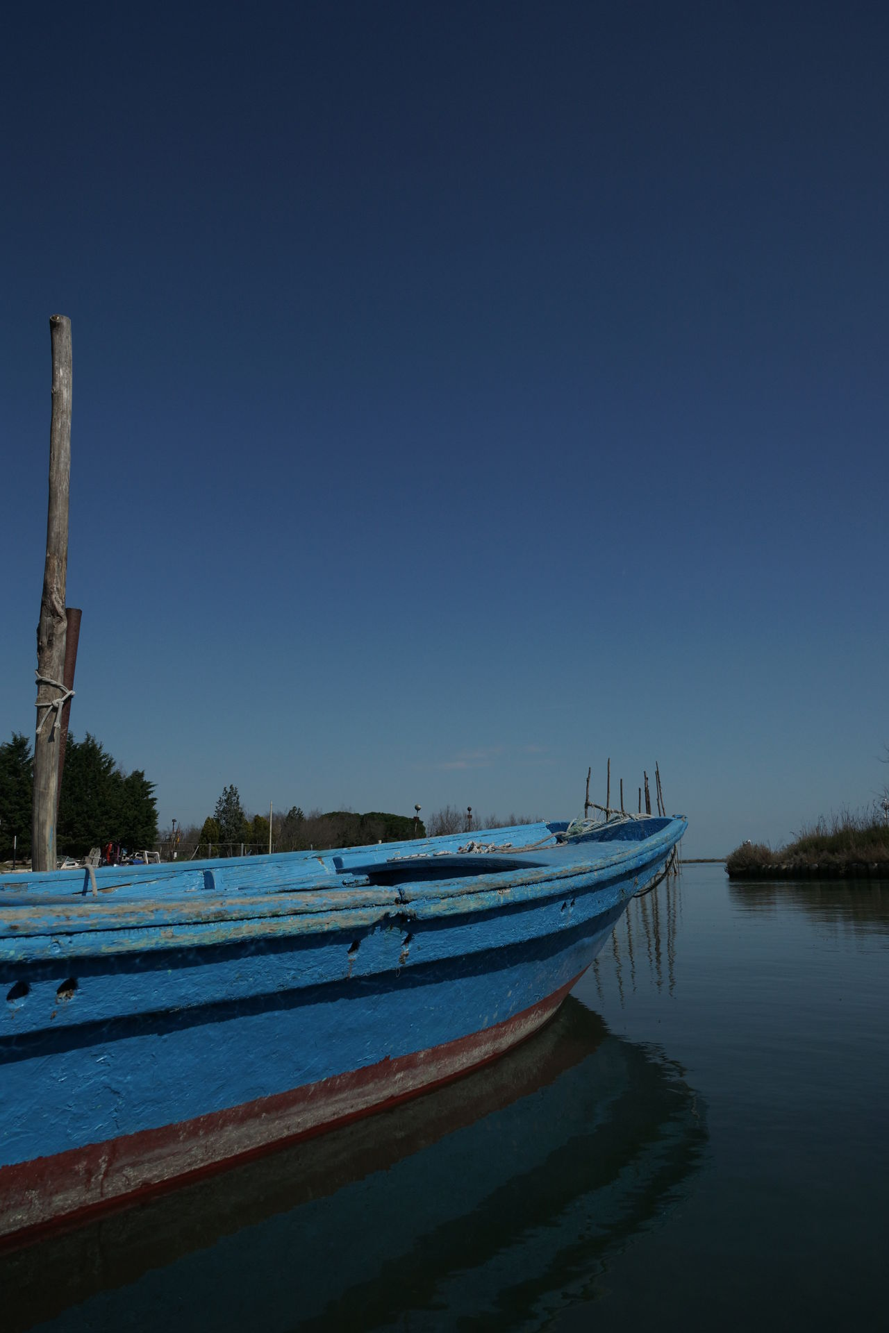 Fishing boat in Torcello, near Venice Anchored Anchored Boats Beauty In Nature Blue Blue Sky Boat Canal Channel Clear Sky Day Fishing Boat Mode Of Transport Moored Nature Nautical Vessel No People Outdoors Scenics Sky Torcello Tranquil Scene Tranquility Transportation Venice Water