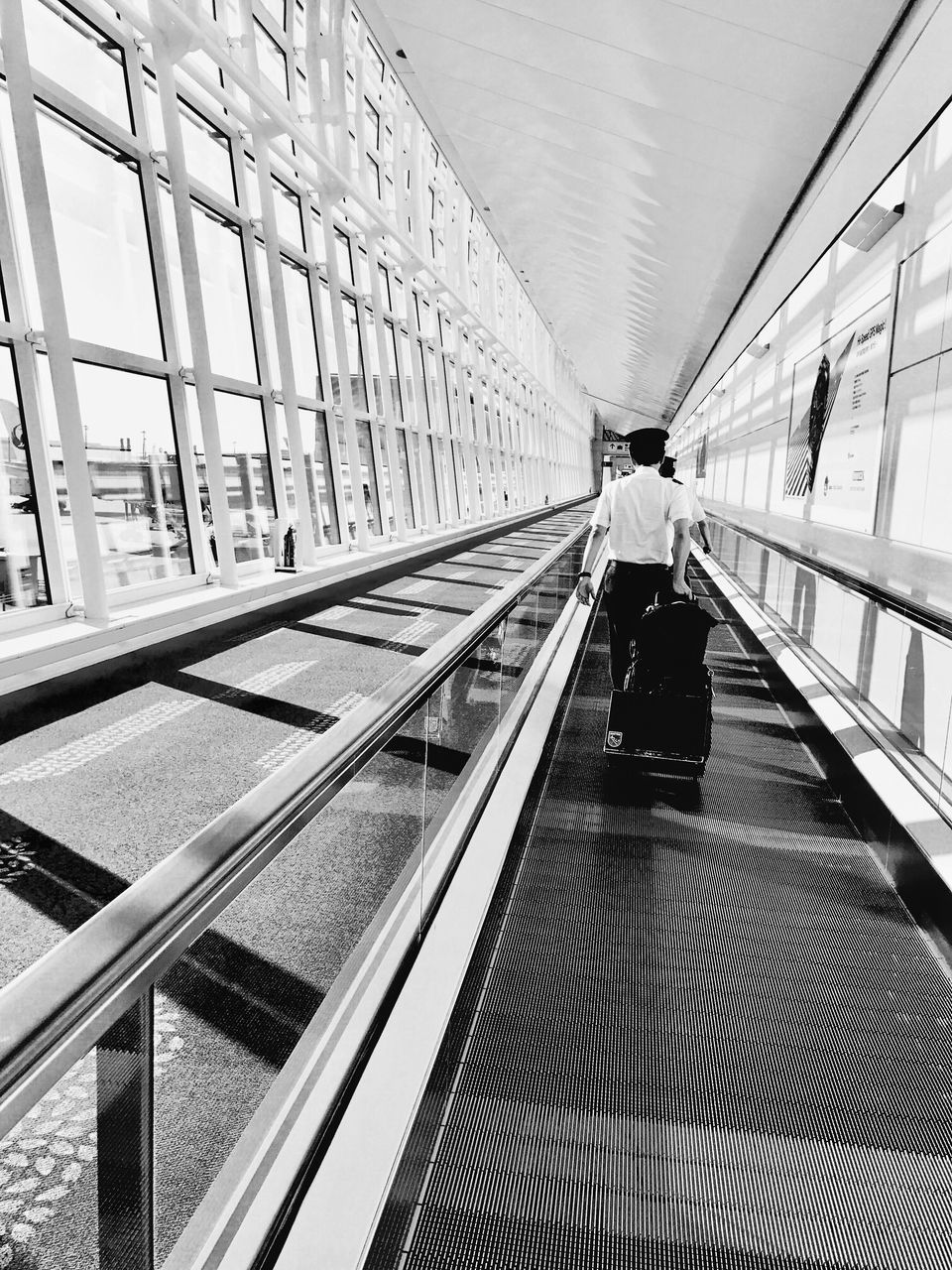 rear view, real people, indoors, architecture, walking, full length, transportation, one person, built structure, men, passenger, women, luggage, modern, airport, journey, lifestyles, technology, futuristic, day, adult, people
