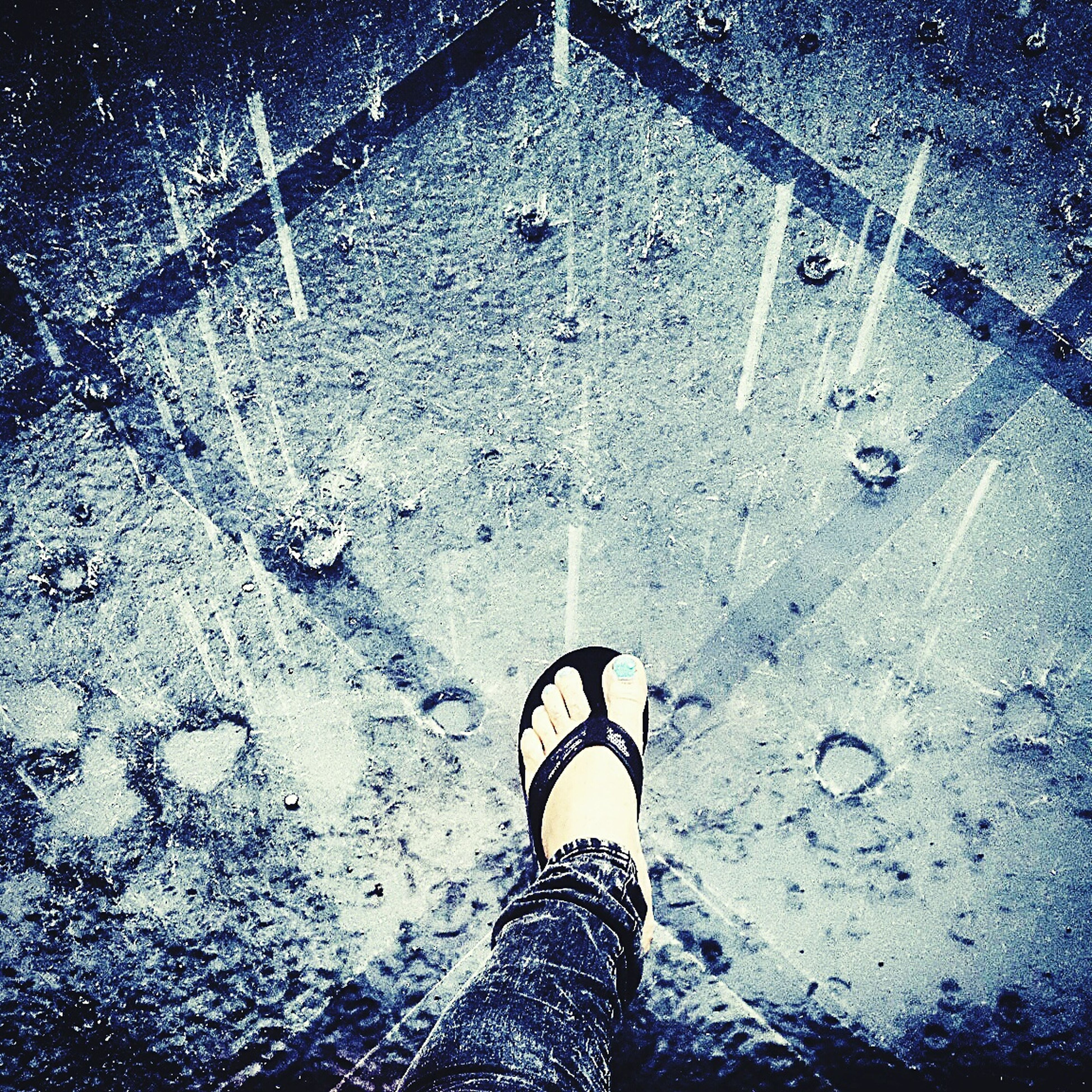 low section, person, street, high angle view, wet, puddle, standing, shoe, rain, personal perspective, lifestyles, road, men, season, unrecognizable person, transportation, asphalt