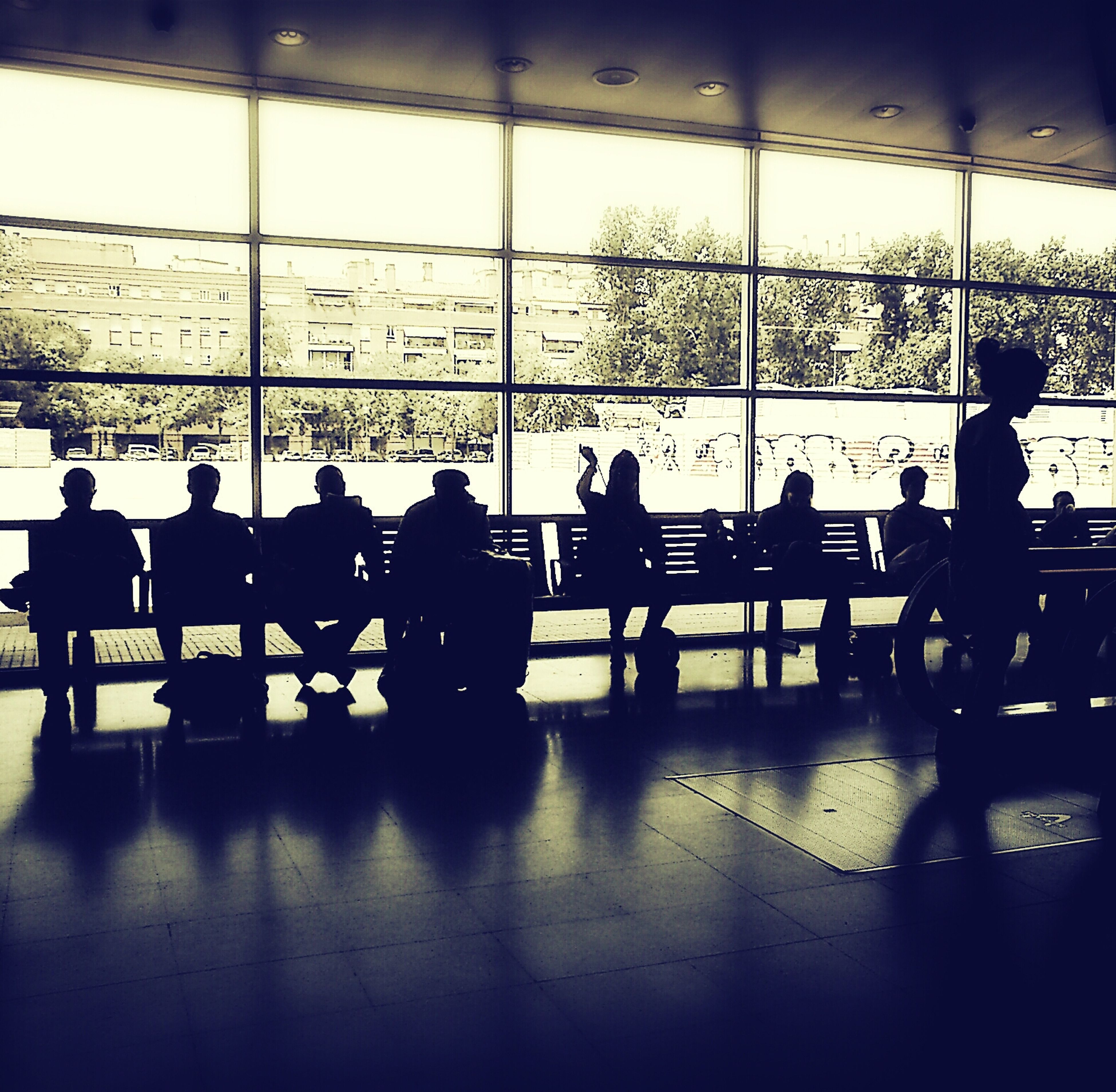 indoors, men, airport, silhouette, person, window, lifestyles, large group of people, glass - material, medium group of people, chair, sitting, leisure activity, transparent, waiting, city, tiled floor, transportation