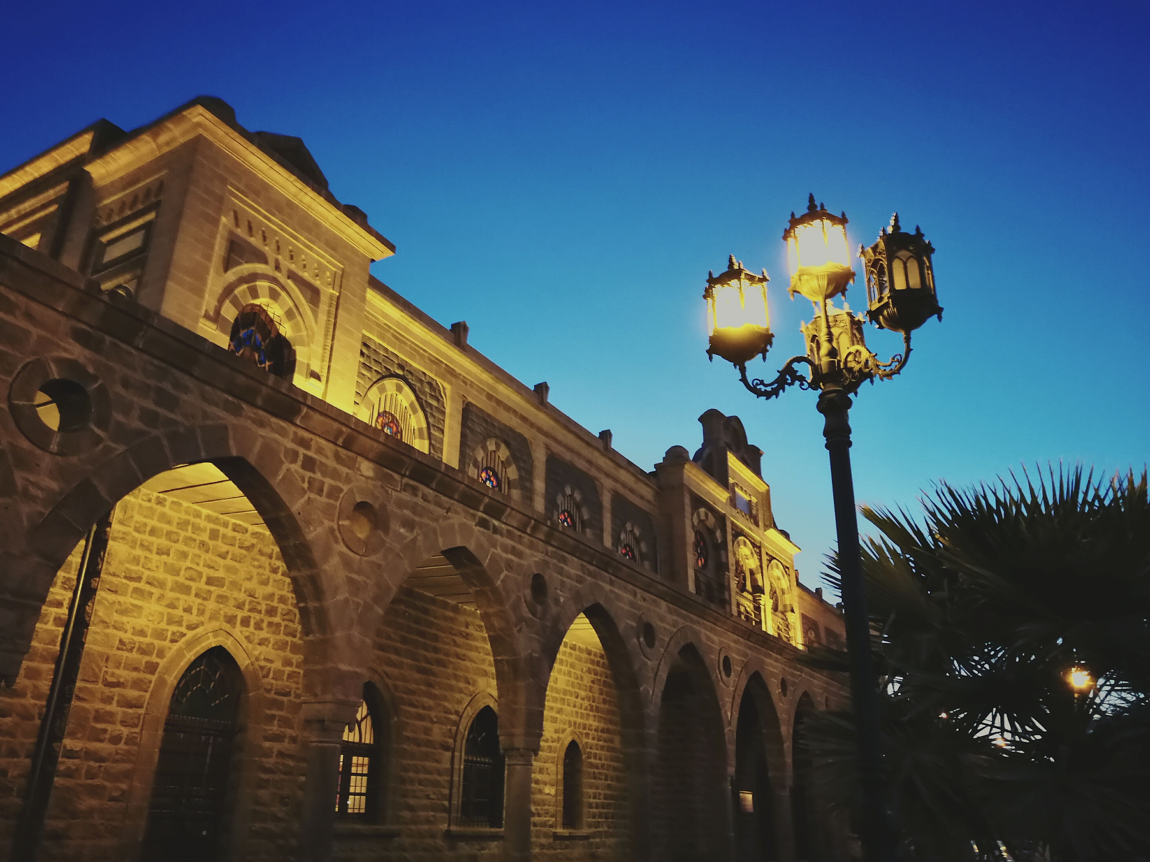 architecture, built structure, clear sky, low angle view, street light, illuminated, arch, blue, lighting equipment, sky, outdoors, facade, travel destinations, city, no people, architectural column, electric lamp, ornate, tourism