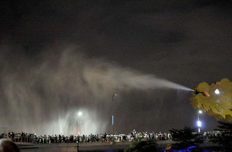 Dragon Bridge spouting water in Da Nang, Vietnam. Attractions Bridges Crowd Da Nang Design Dragon Bridge Dragons Engineering Entertainment Excitement Night Outdoors Sky Spray Tourism Vietnam Water Water Spouts