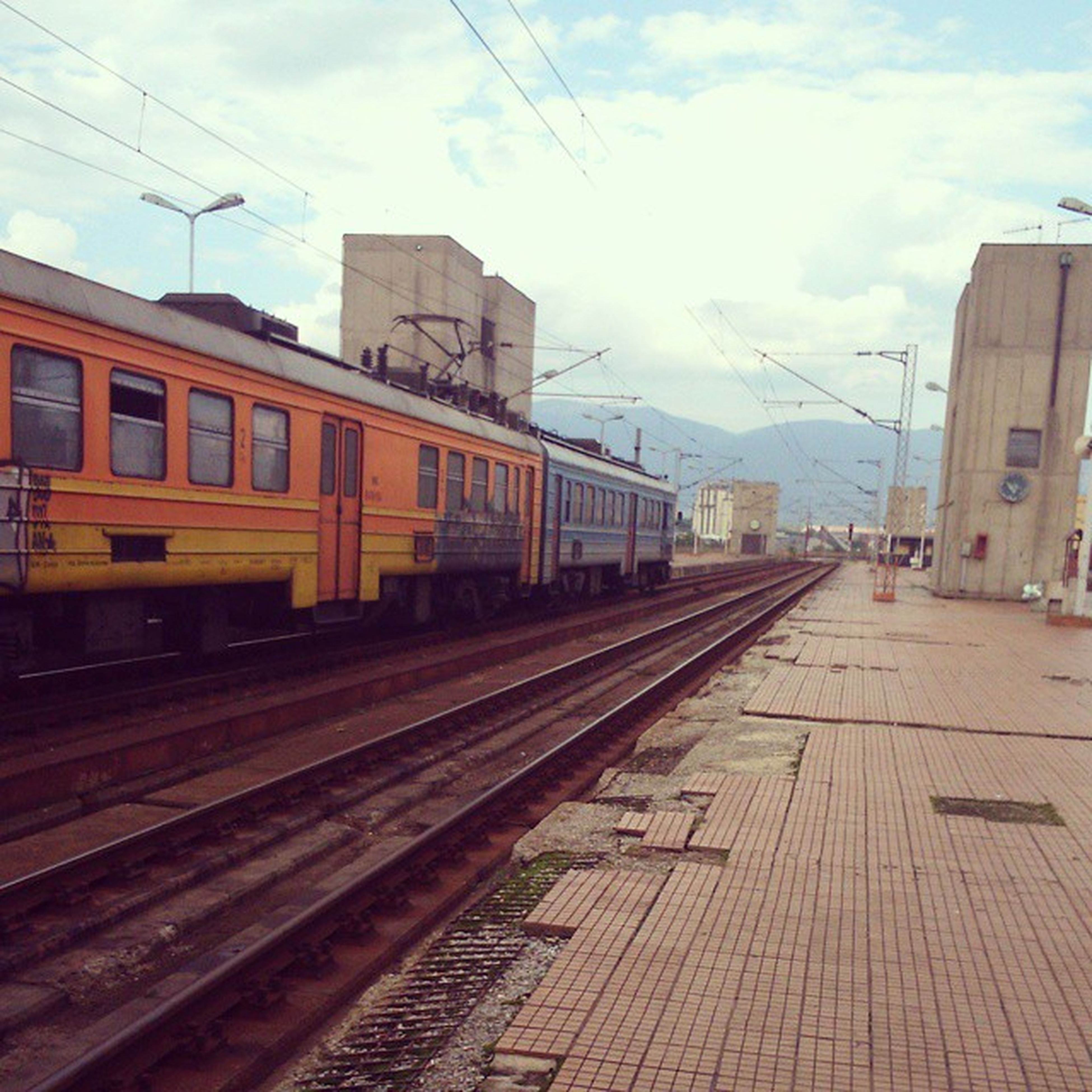 railroad track, rail transportation, public transportation, building exterior, railroad station, railroad station platform, transportation, built structure, architecture, power line, sky, city, the way forward, train - vehicle, diminishing perspective, railway track, tramway, electricity pylon, cable, mode of transport