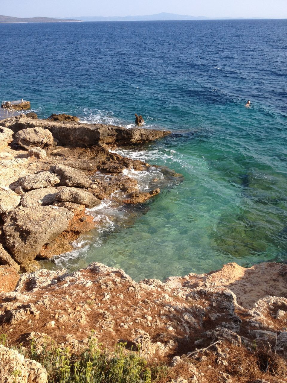 sea, water, horizon over water, beauty in nature, scenics, nature, tranquil scene, rock - object, tranquility, high angle view, day, outdoors, beach, real people, wave, blue, sky