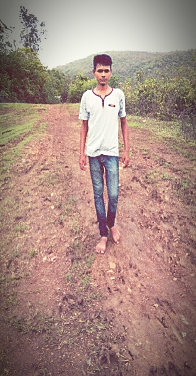 casual clothing, front view, one person, full length, standing, mid adult, looking at camera, real people, portrait, smiling, young adult, grass, outdoors, landscape, happiness, day, tree, nature, one man only, only men, adult, adults only, people