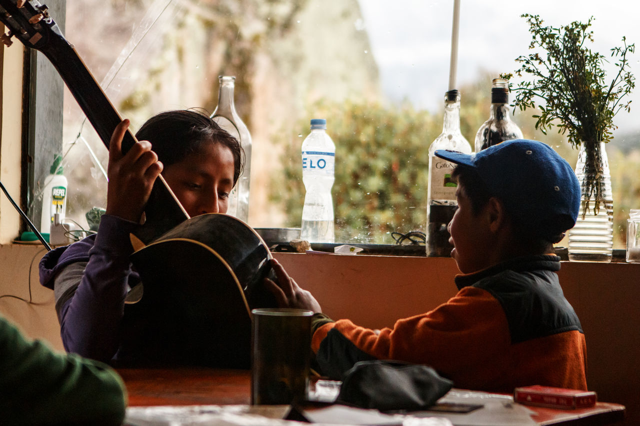 Kids taking refuge from a rainstorm inside a rural vounteer-drivem eco-hostel in the Andes Mountains. Andes Charity Charity And Relief Work Childhood Children Kids Kids Being Kids Moments Music Music Brings Us Together Musical Instrument People Person Relief Volunteering