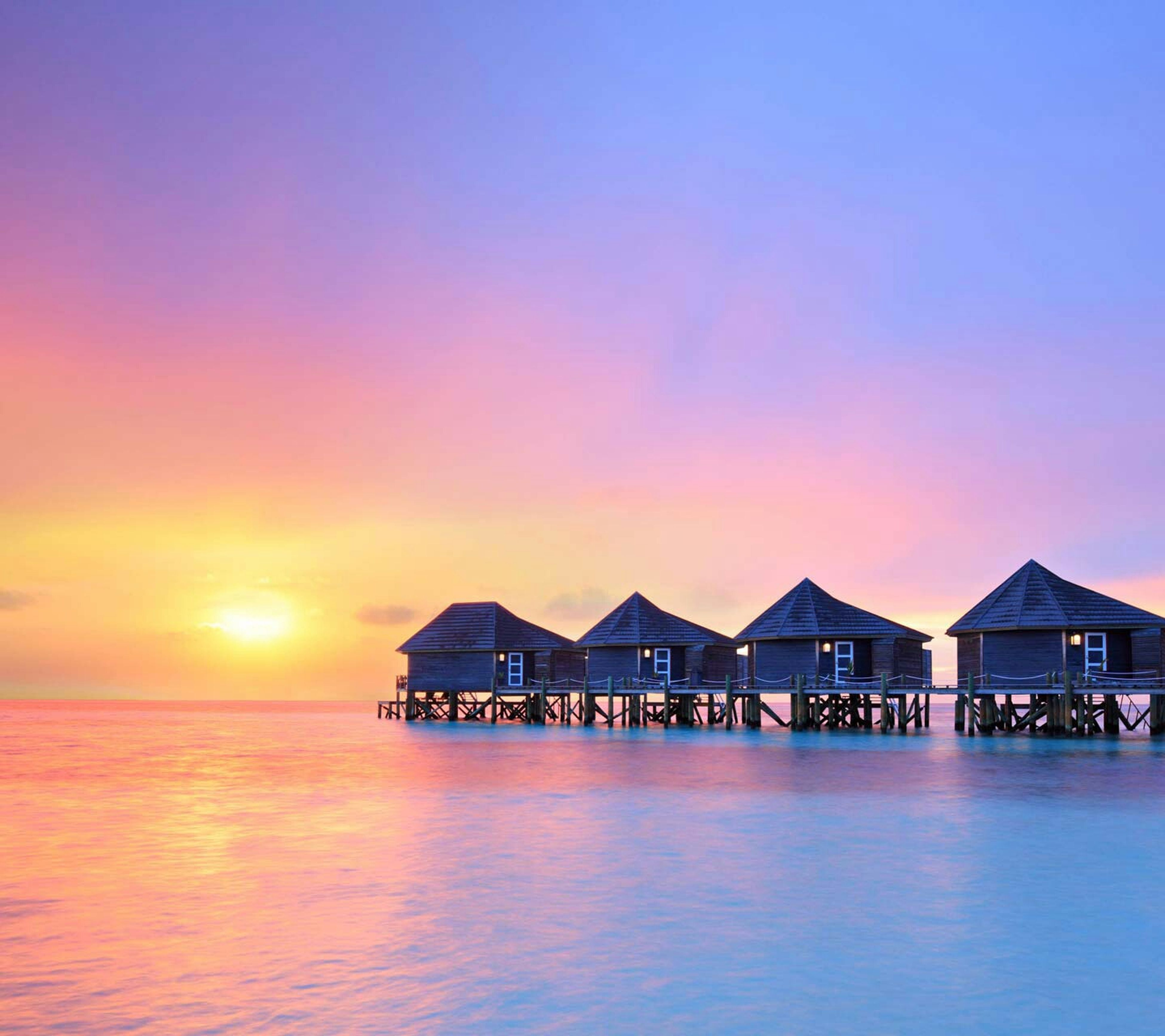 water, sunset, sea, waterfront, built structure, architecture, copy space, building exterior, clear sky, scenics, orange color, tranquility, tranquil scene, beauty in nature, horizon over water, sky, reflection, nature, idyllic, sun