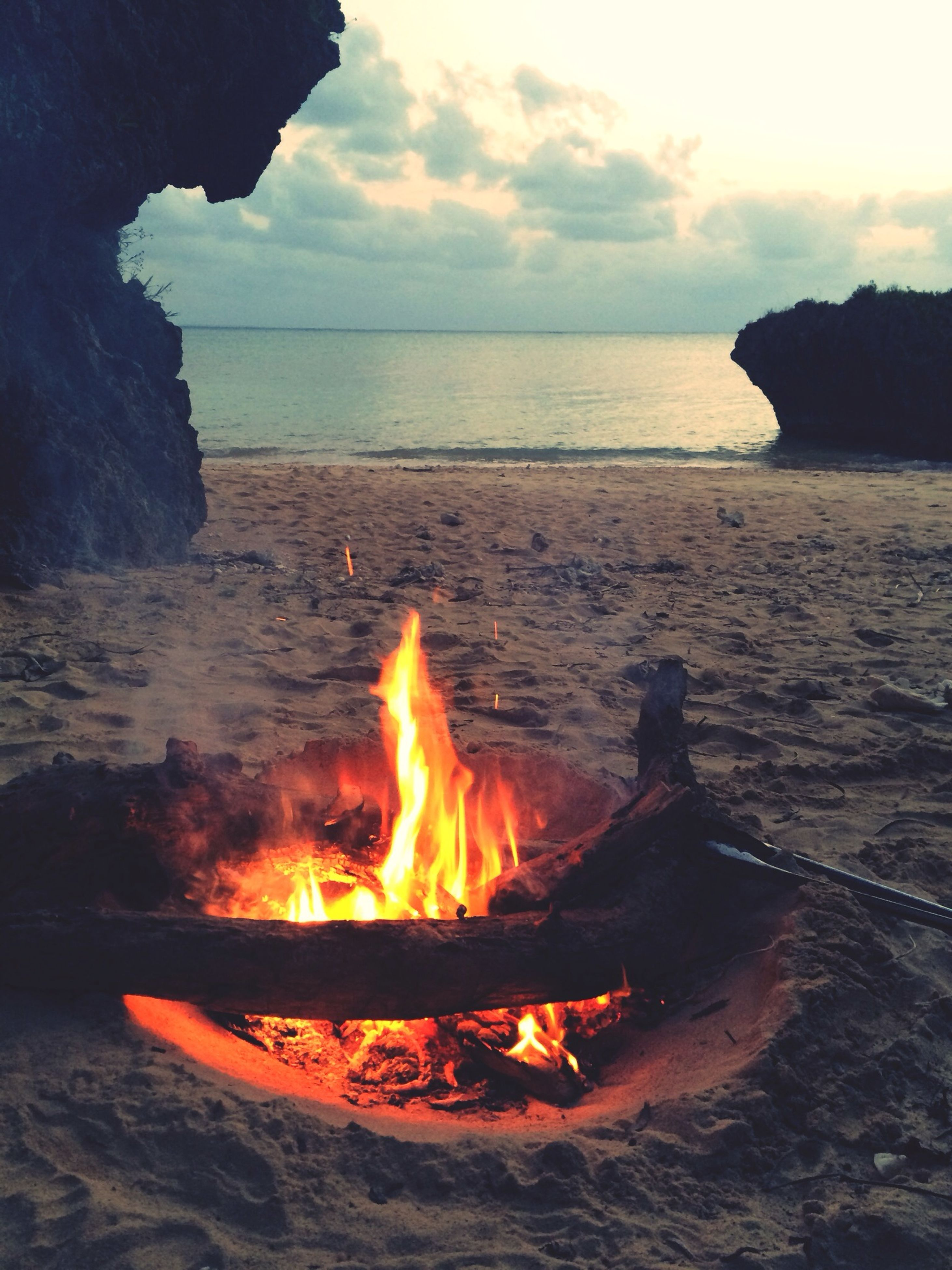 flame, burning, sunset, fire - natural phenomenon, heat - temperature, water, orange color, sea, bonfire, sun, scenics, rock - object, beach, beauty in nature, rock formation, fire, campfire, tranquil scene, heat, sky