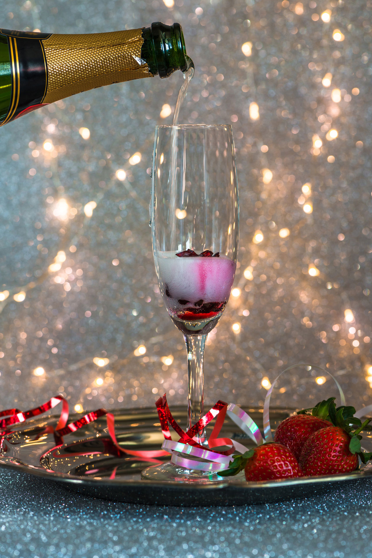 Champagne poured into glass with hibiscus flower inside and strawberries on festive background Background Beauty In Nature Birthday Celebration Bottle Of Champagne Bubbles Celebration Champagne Champagne Flute Champagne Glasses Christmas Festive Background Glass Hibiscus Flower New Year Celebration Portrait Pour Pouring Sparkle Strawberries
