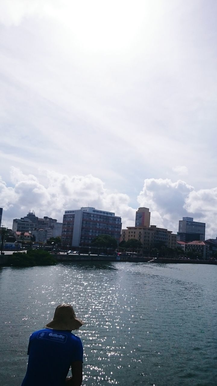 architecture, building exterior, city, built structure, rear view, water, river, sky, cityscape, skyscraper, one person, modern, real people, cloud - sky, outdoors, lifestyles, day, nature, people