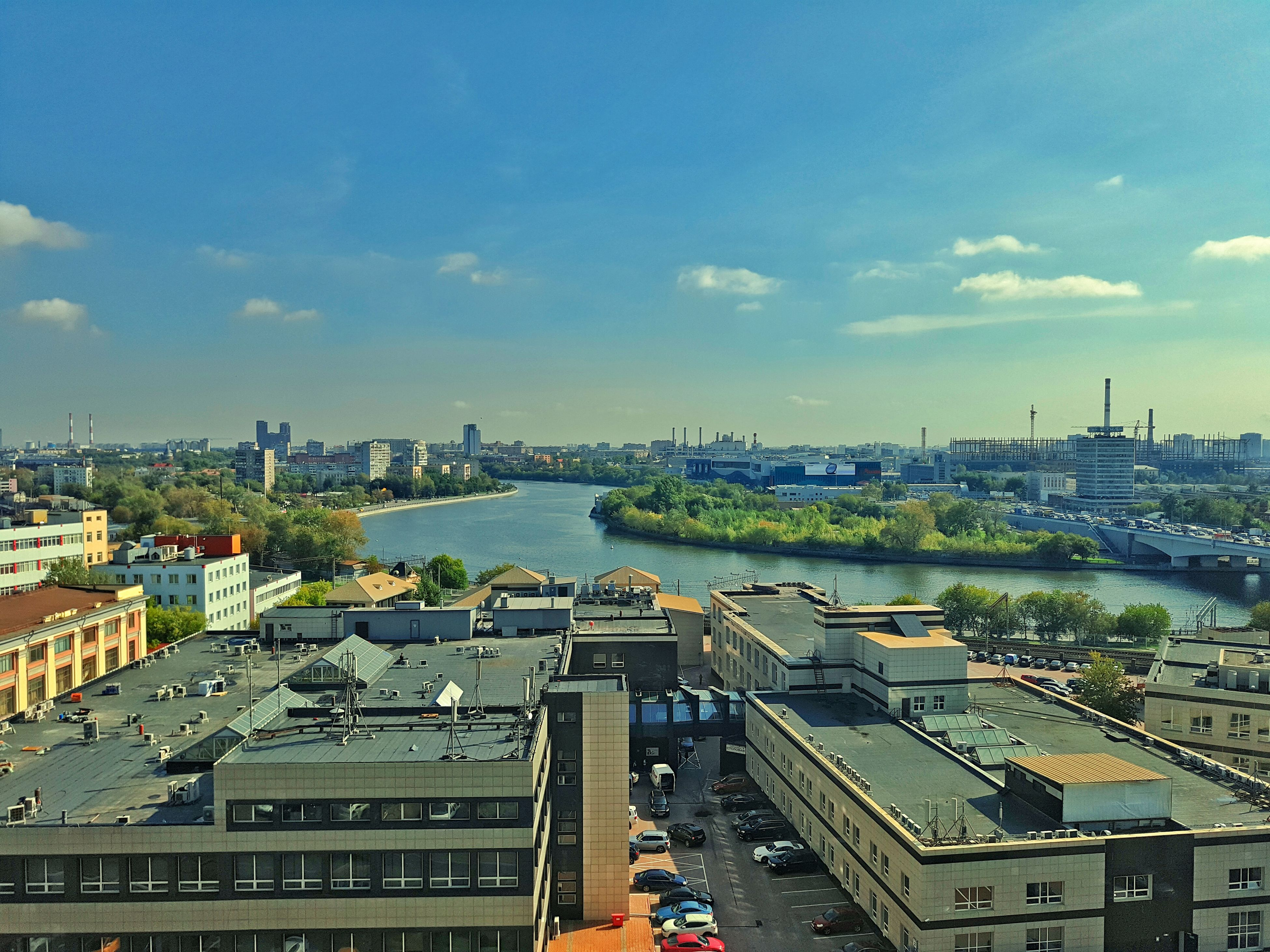 architecture, built structure, building exterior, city, water, river, high angle view, sky, transportation, bridge - man made structure, cityscape, mode of transport, cloud - sky, waterfront, day, cloud, engineering, riverbank, development, city life, outdoors, office building, capital cities, bridge