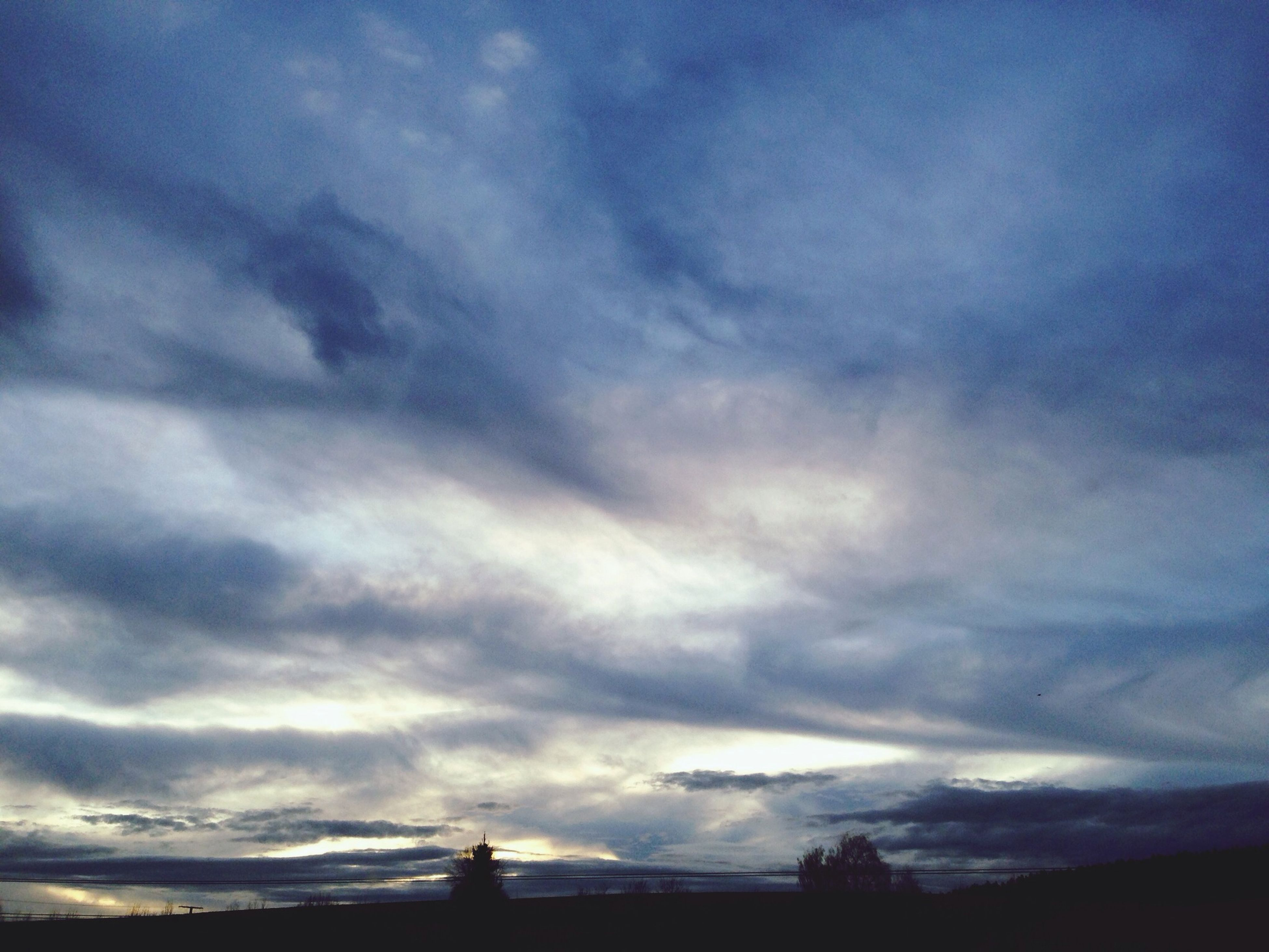 sky, silhouette, cloud - sky, low angle view, cloudy, built structure, architecture, cloud, building exterior, dusk, sunset, weather, beauty in nature, nature, scenics, tranquility, overcast, outdoors, dramatic sky, cloudscape