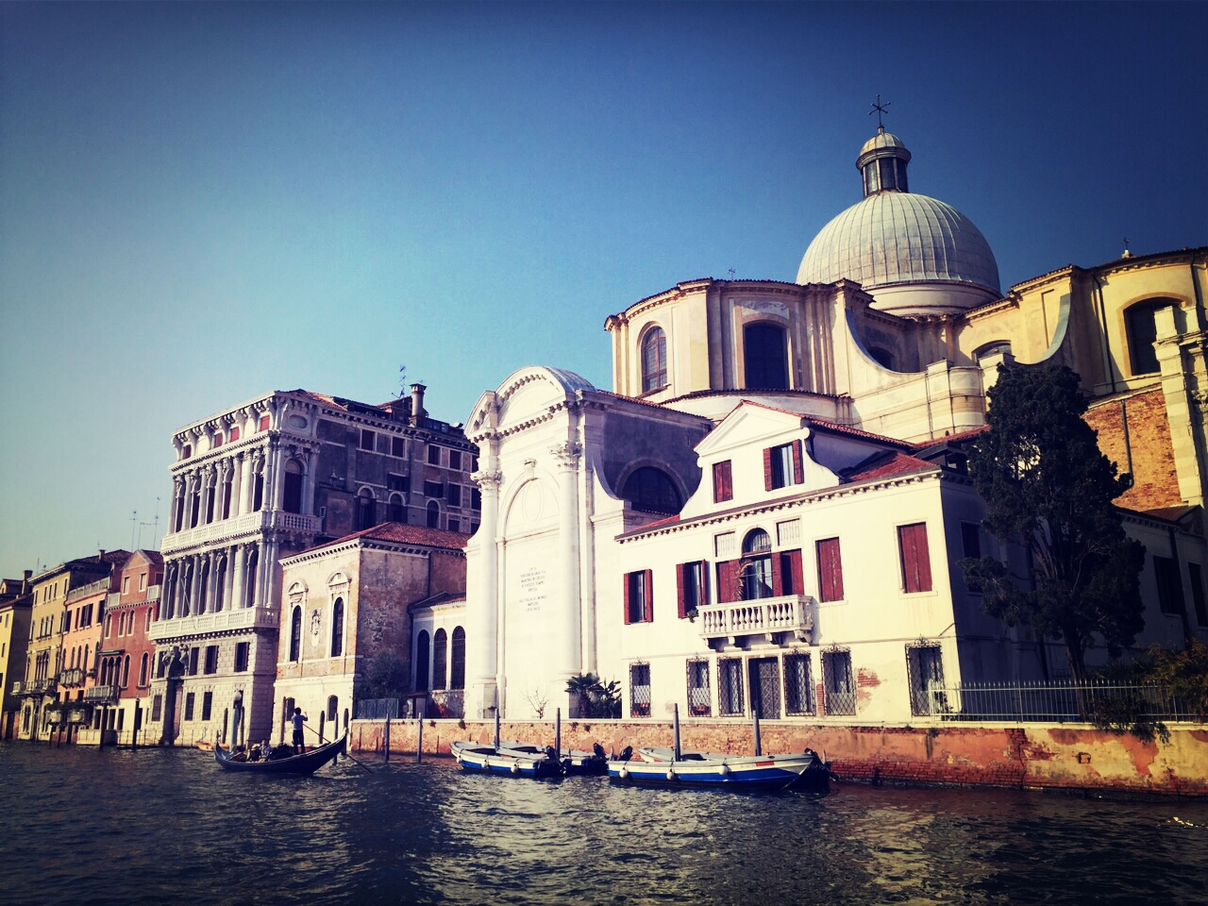 building exterior, architecture, built structure, water, waterfront, nautical vessel, clear sky, transportation, boat, mode of transport, dome, church, canal, blue, old town, residential structure, sea, religion, residential building, city