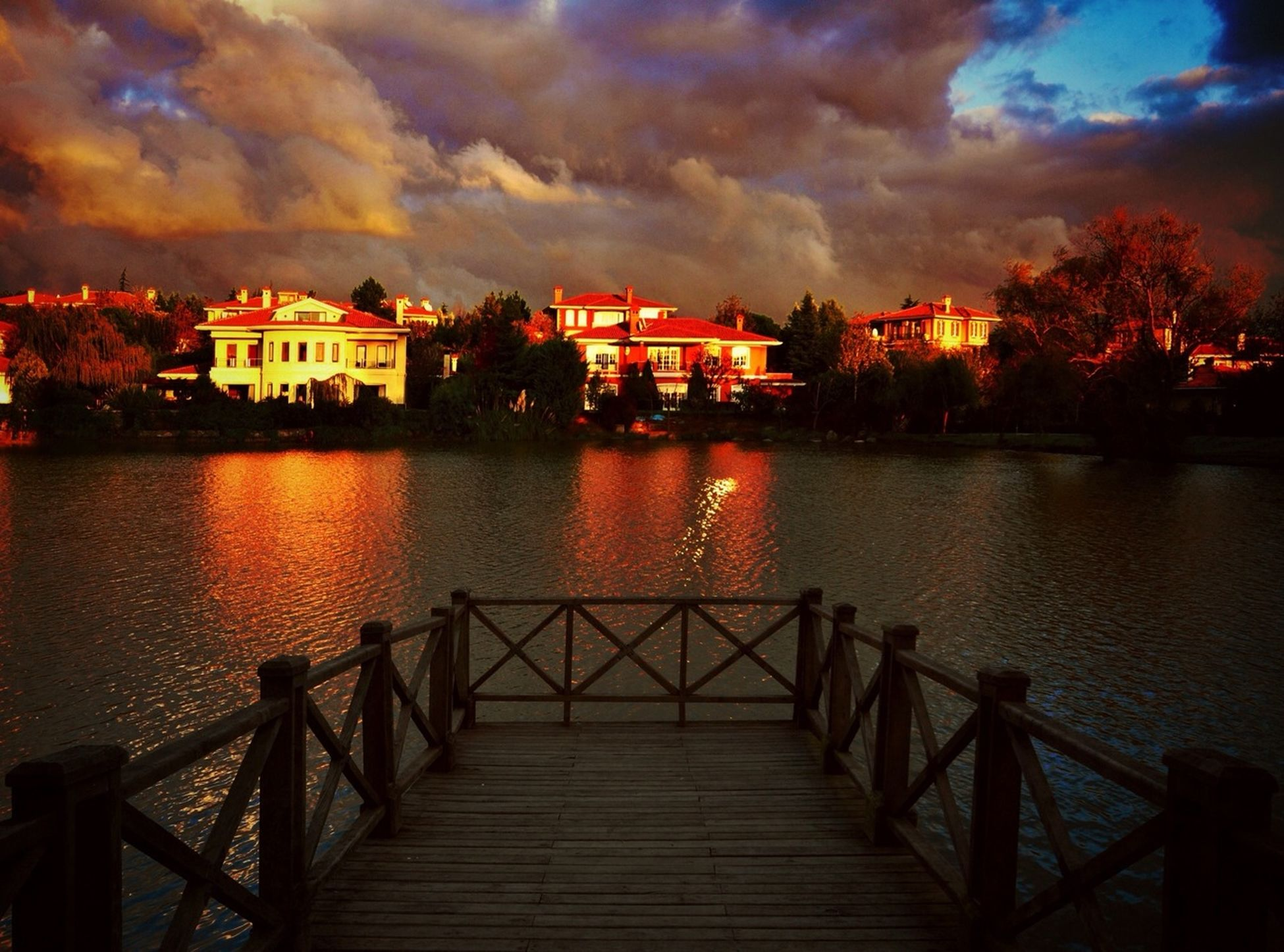architecture, built structure, water, sky, building exterior, cloud - sky, sunset, river, reflection, railing, cloudy, cloud, lake, dusk, waterfront, pier, connection, house, illuminated, nature
