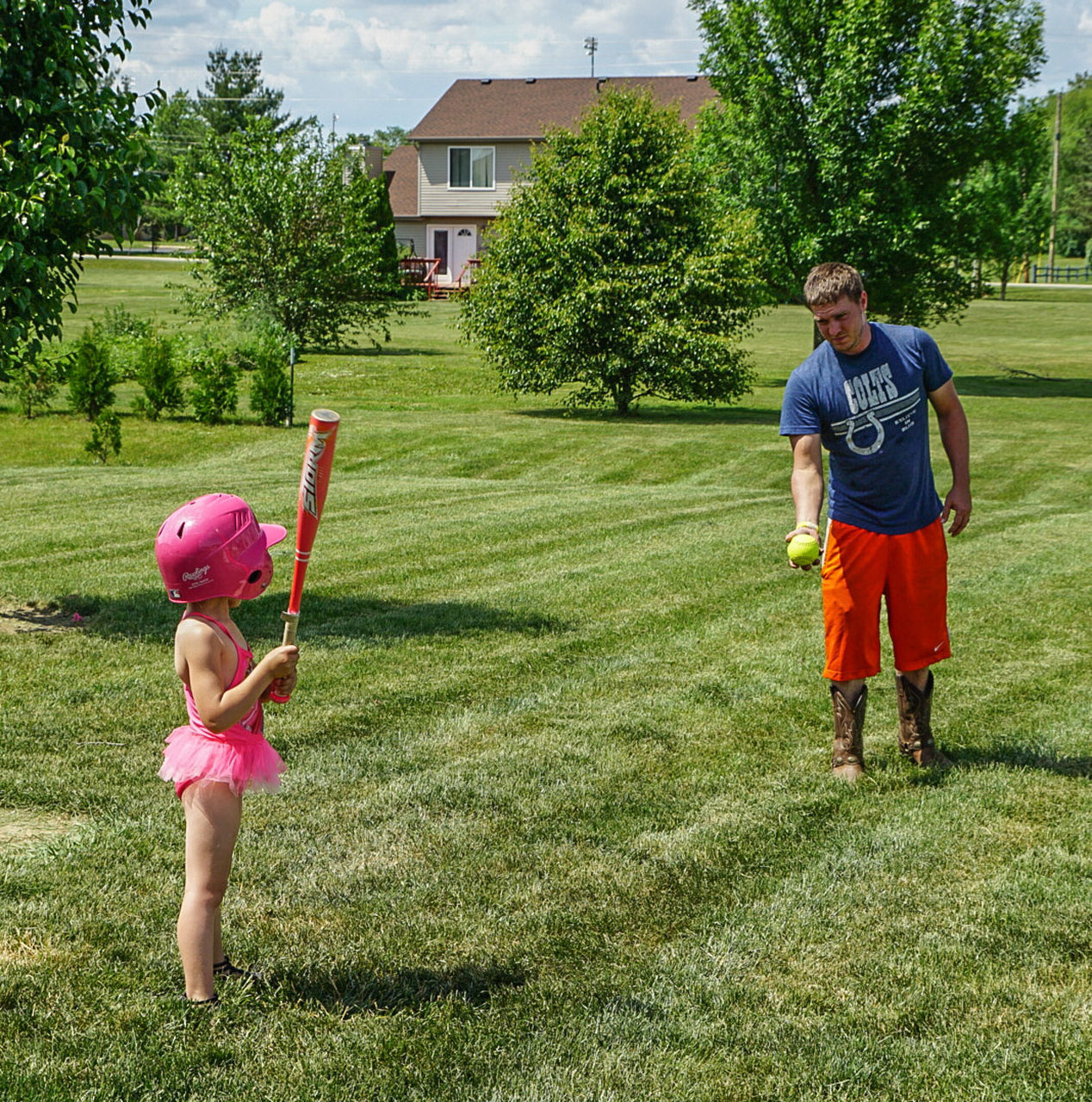 Father Playing Baseball With Daughter While Standing In Lawn