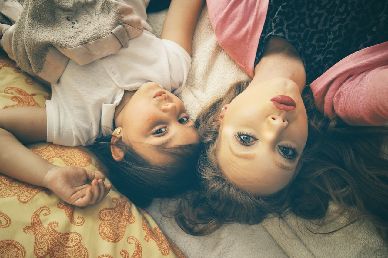 Looking At Camera Lying Down Girls Child Childhood Togetherness Indoors  Portrait Two People Real People Bed Home Interior Love Relaxation Lying On Back Embracing Friendship Sibling Cute Smiling
