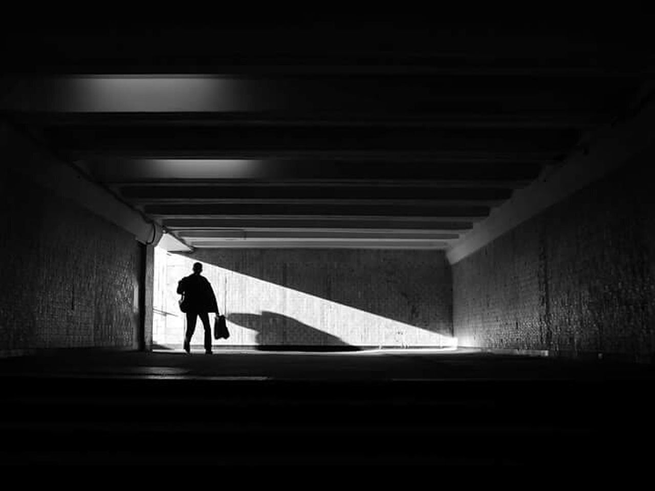 one person, full length, silhouette, walking, architecture, built structure, tunnel, transportation, mystery, road, loneliness, real people, the way forward, one man only, men, standing, day, illuminated, outdoors, adult, parking garage, people, adults only