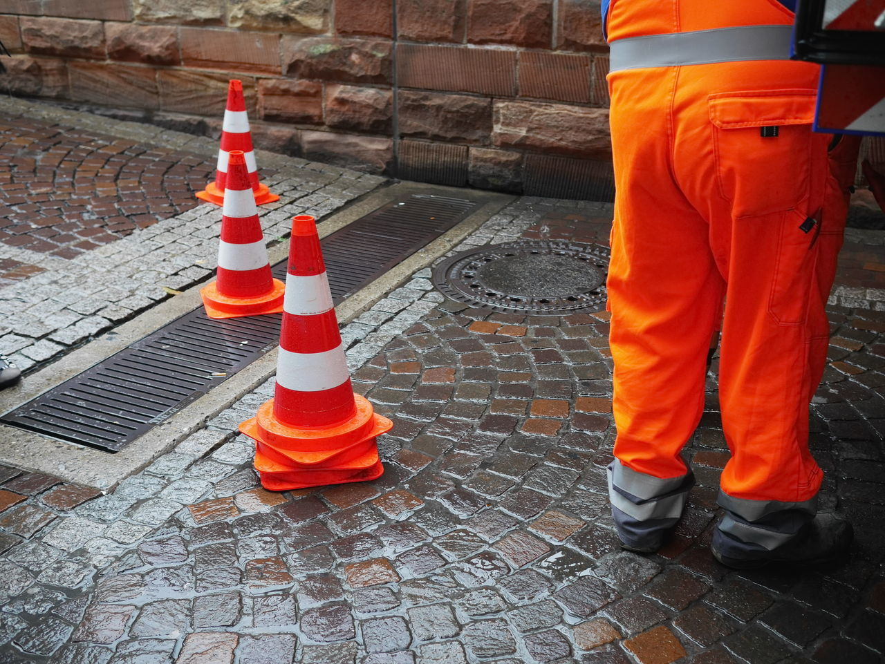 Adult Adults Only Day Human Body Part Low Section Men Occupation One Man Only One Person Outdoors People Real People Reflective Clothing Repairing Road Construction Safety Standing Traffic Cone Working