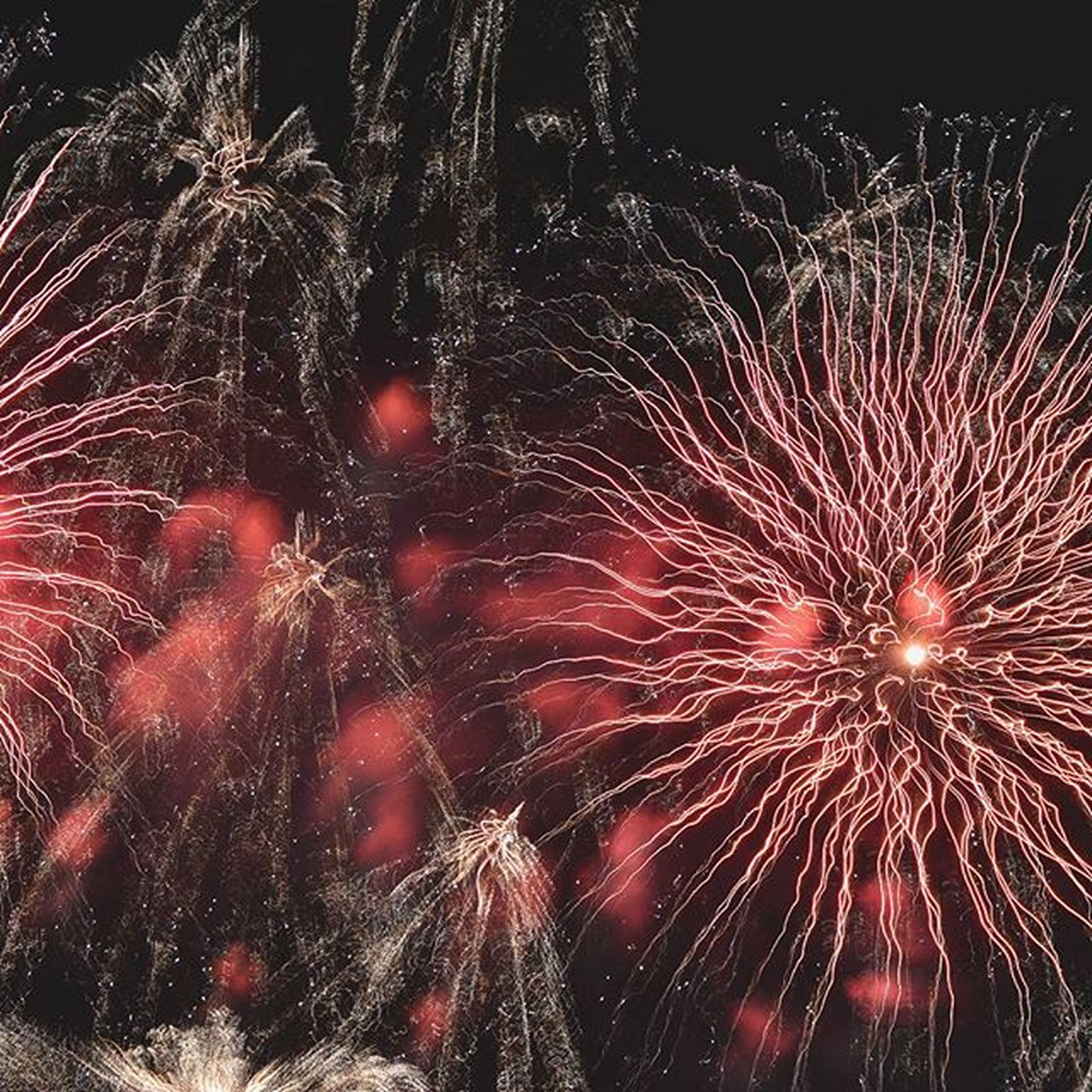 night, celebration, illuminated, firework display, long exposure, exploding, low angle view, motion, glowing, firework - man made object, sparks, event, arts culture and entertainment, red, blurred motion, firework, celebration event, entertainment, sky, outdoors