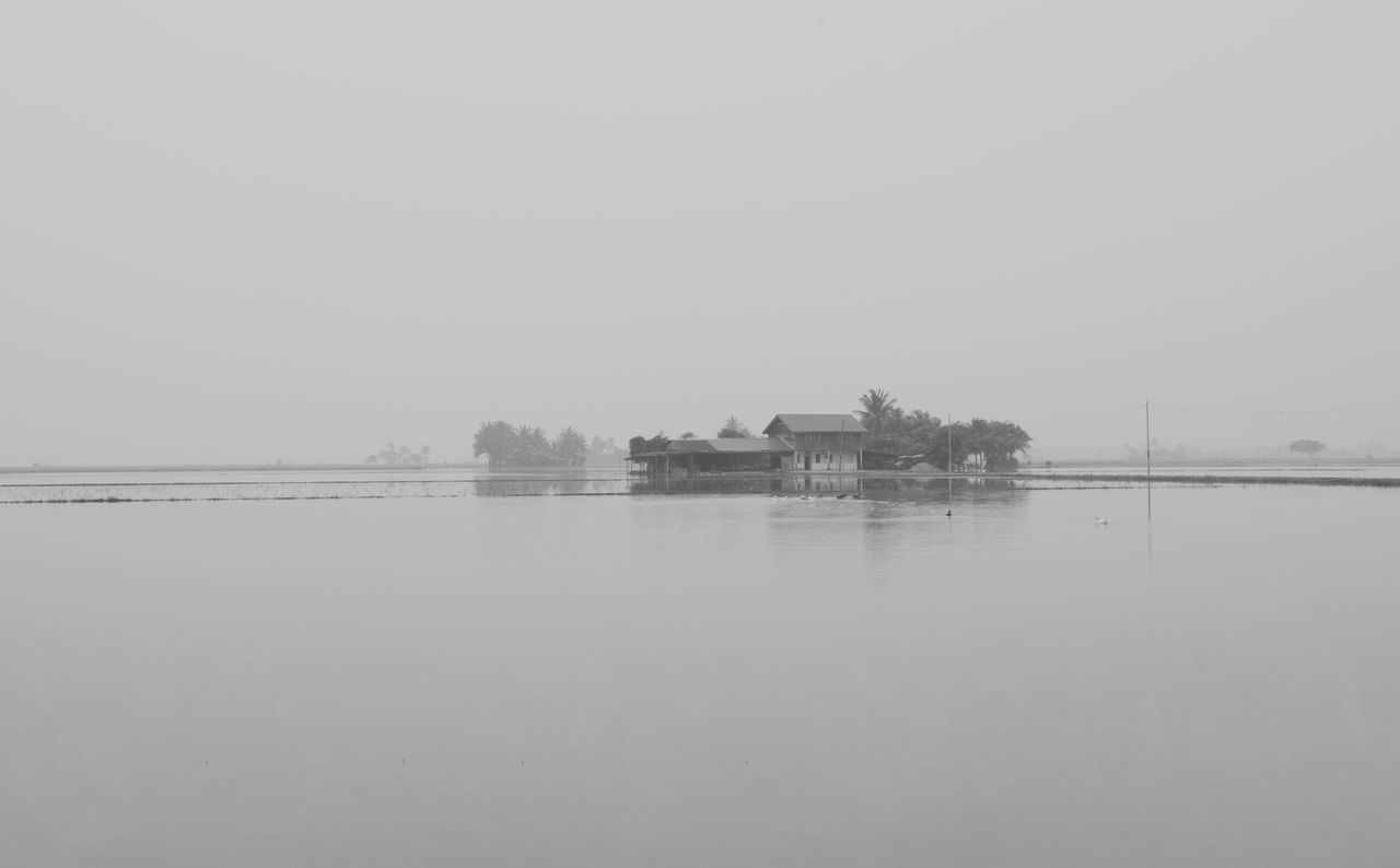 A view of house during haze. Architecture Beauty In Nature Built Structure Clear Sky Day Haze Lake Minimalism Nature Nautical Vessel No People Outdoors Reflection Scenics Sky Tranquil Scene Tranquility Tree Water