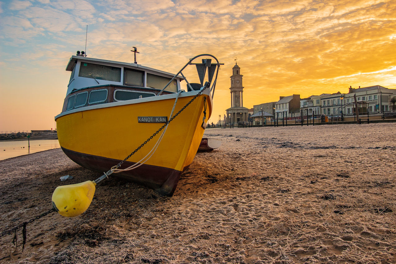 nautical vessel, transportation, mode of transport, sky, beach, boat, moored, sea, sunset, outdoors, water, cloud - sky, nature, no people, yellow, sand, tranquility, beauty in nature, day, scenics, horizon over water